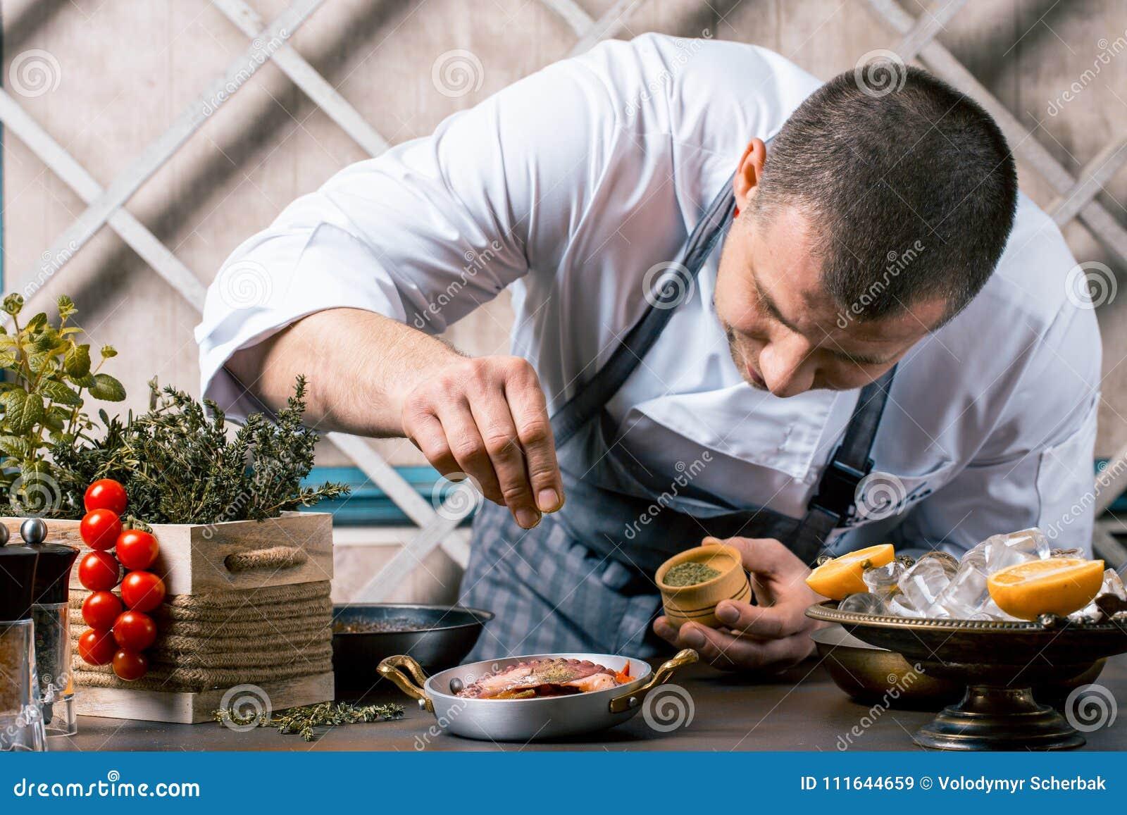 Chef-kok die kruiden op schotel in commerciële keuken bestrooien Gastronomisch restaurant