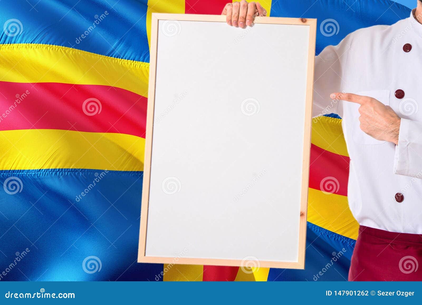 Chef-kok die leeg whiteboardmenu op Aland-de achtergrond van de Eilandenvlag houden Kok die eenvormige richtende ruimte voor teks