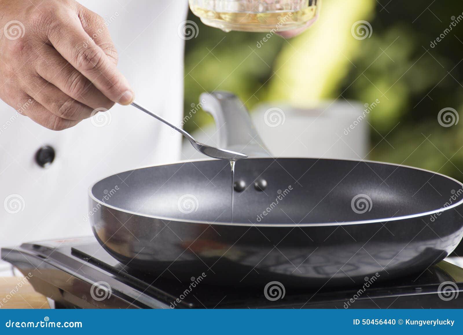 Chef-kok die plantaardige olie gieten aan de pan