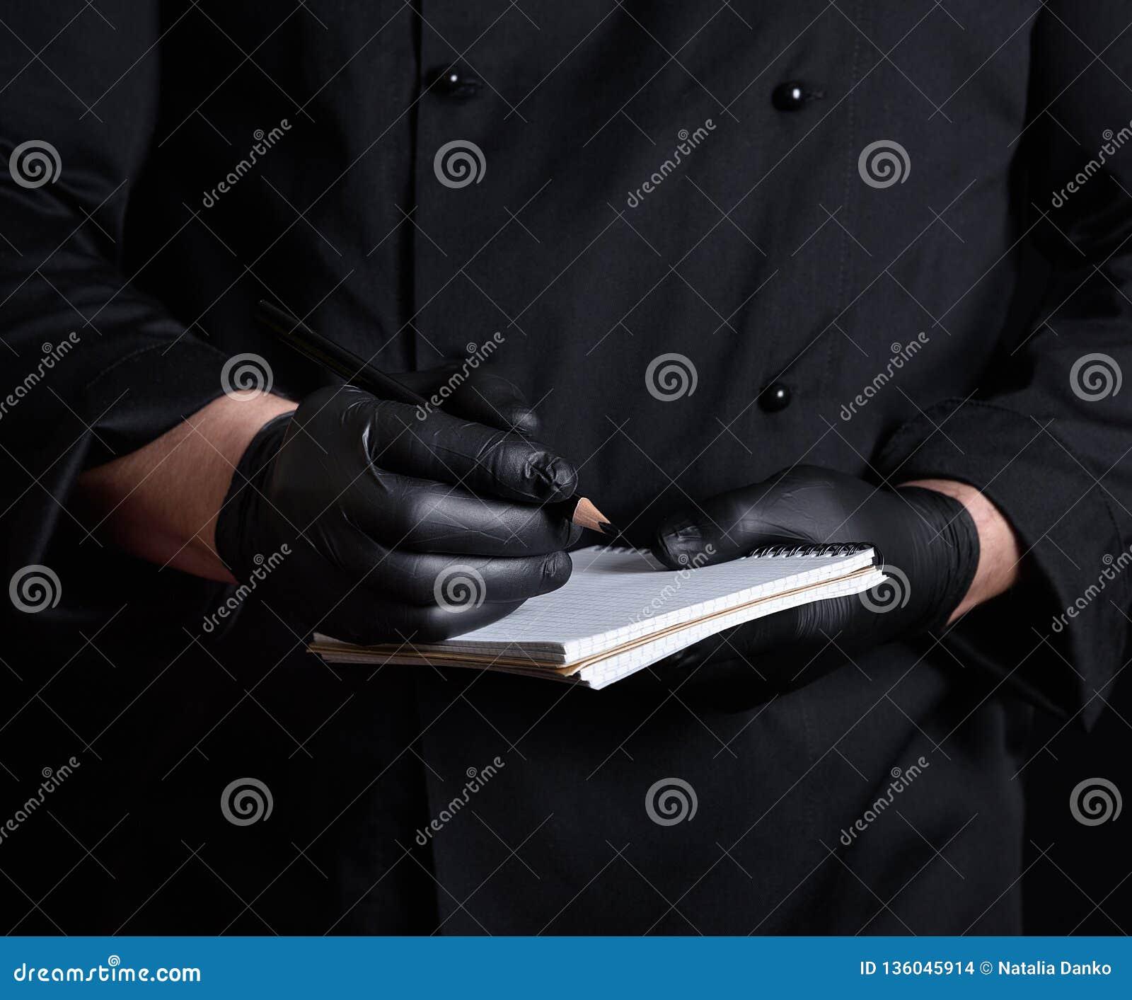 Chef-kok die in zwarte eenvormige en latexhandschoenen een leeg notitieboekje en een zwart houten potlood houden