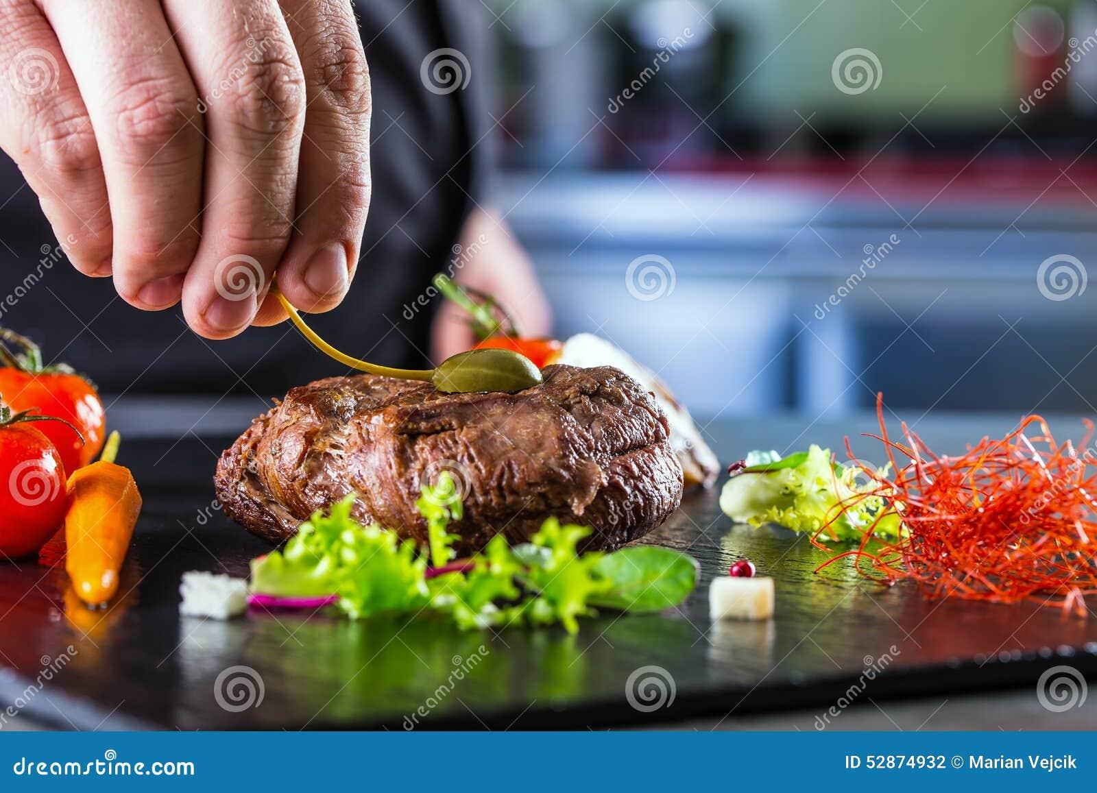 Chef-kok in hotel of restaurantkeuken het koken, slechts handen Voorbereid rundvleeslapje vlees met plantaardige decoratie