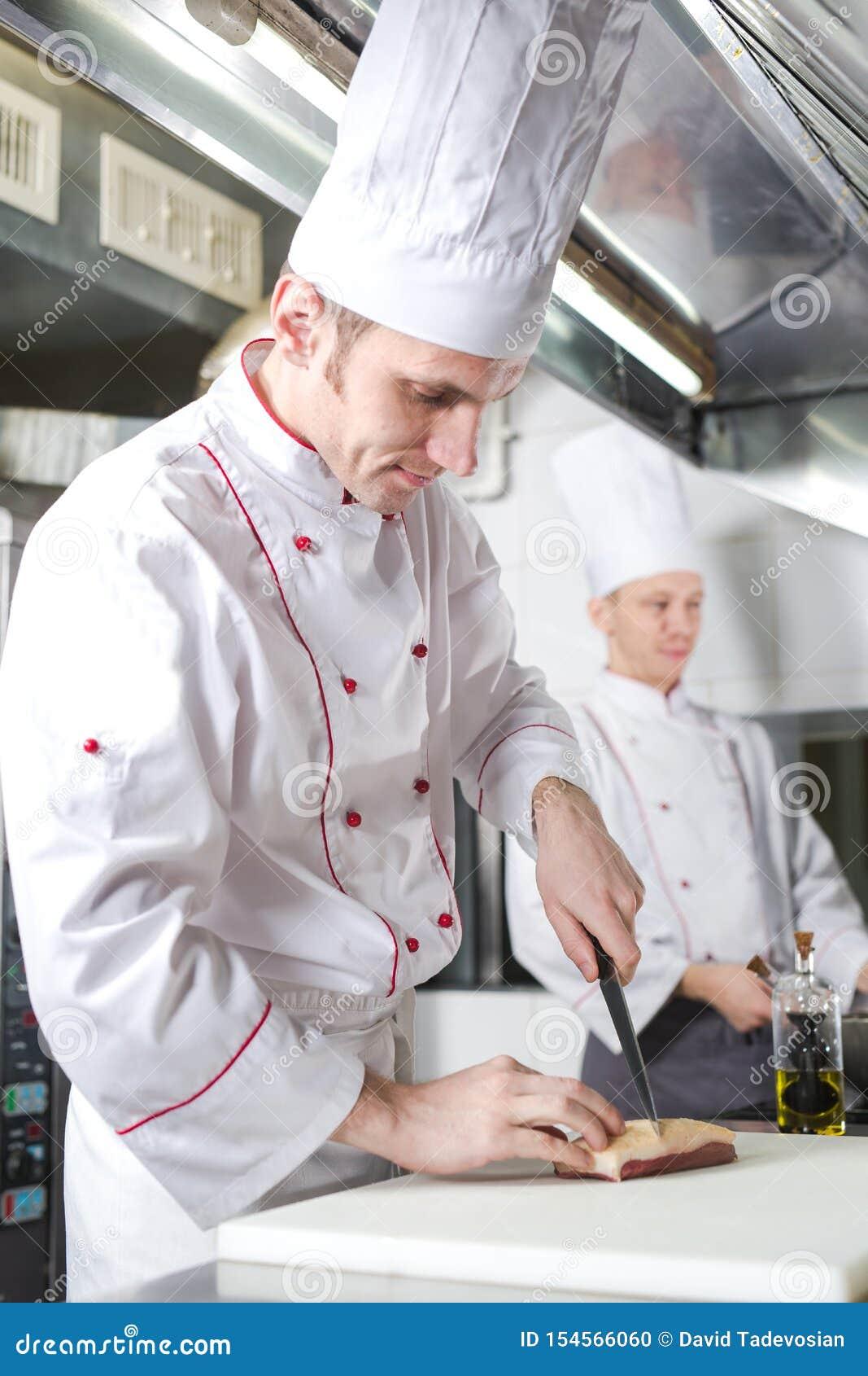Chef-kok scherp vlees op hakbord, het professionele mes van de kokholding en scherp vlees in restaurant