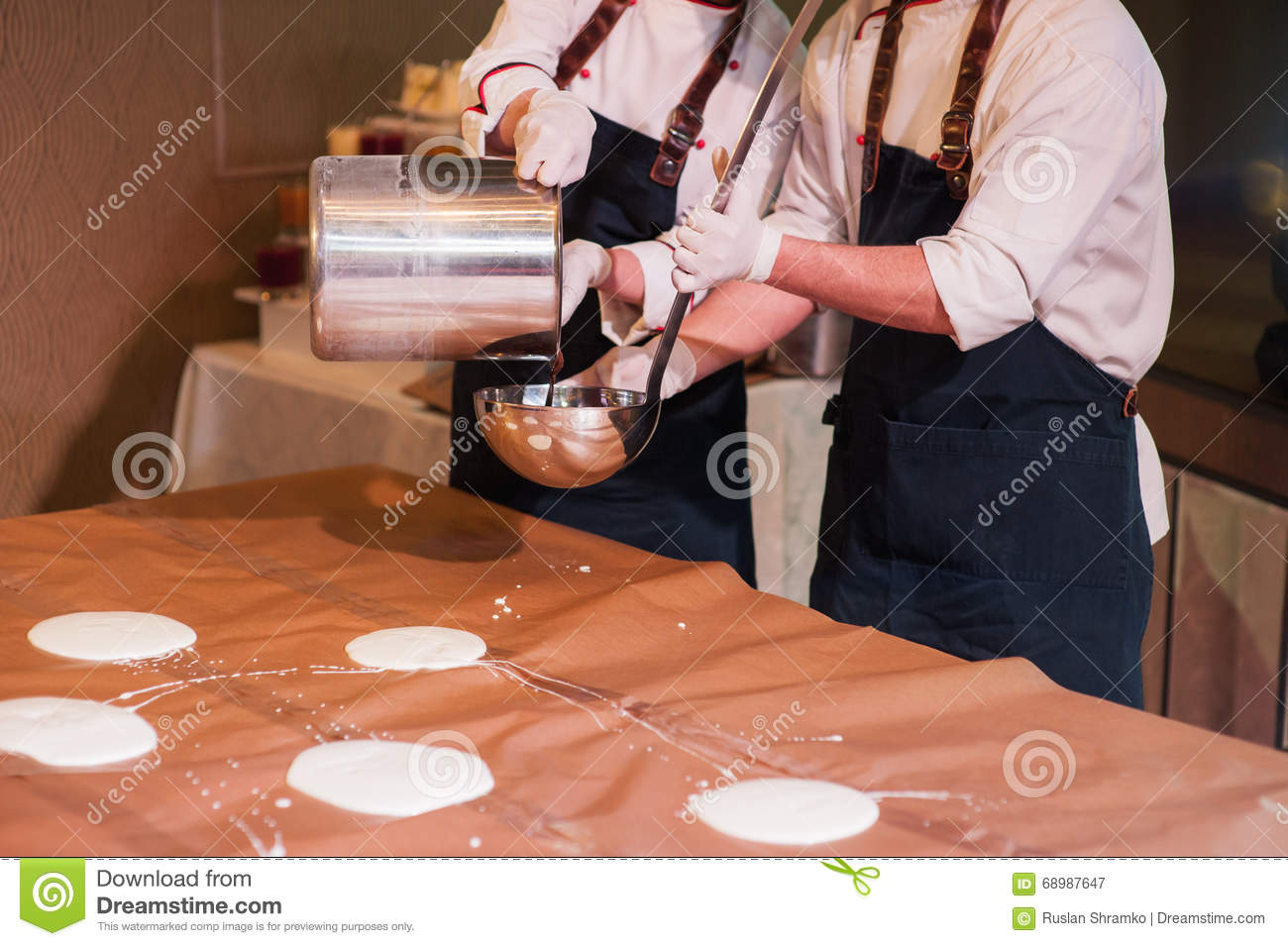 Chef ladle pours big pancakes on the table