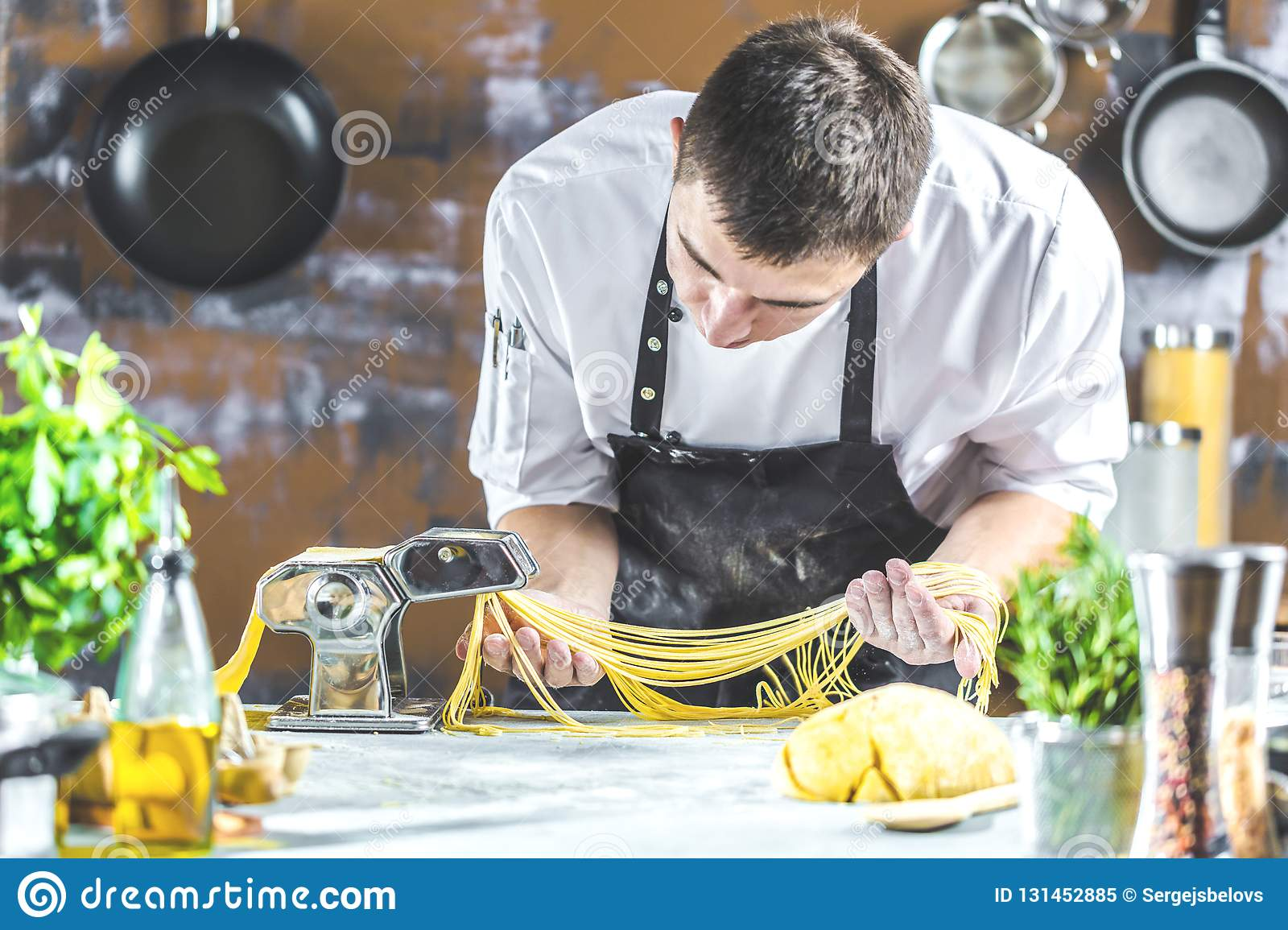 Chef Making Spaghetti Noodles With Pasta Machine On Kitchen ...