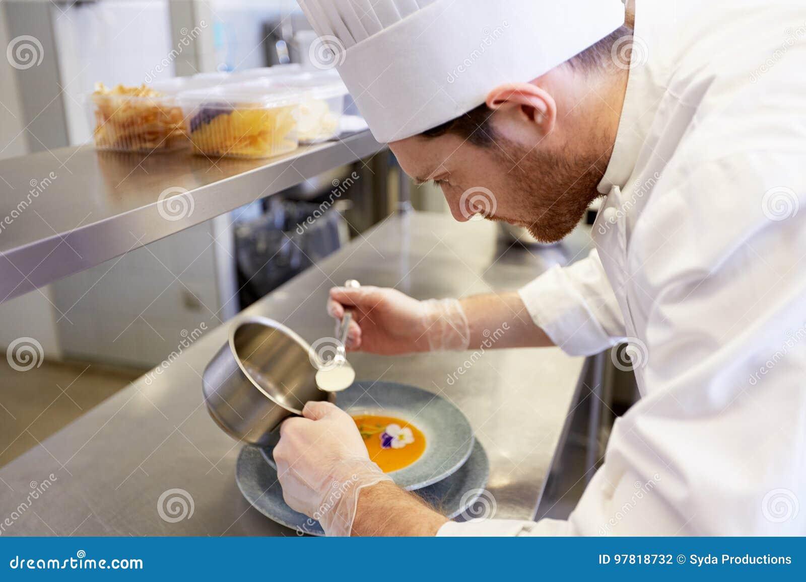 Chef masculin heureux faisant cuire la nourriture à la cuisine de restaurant