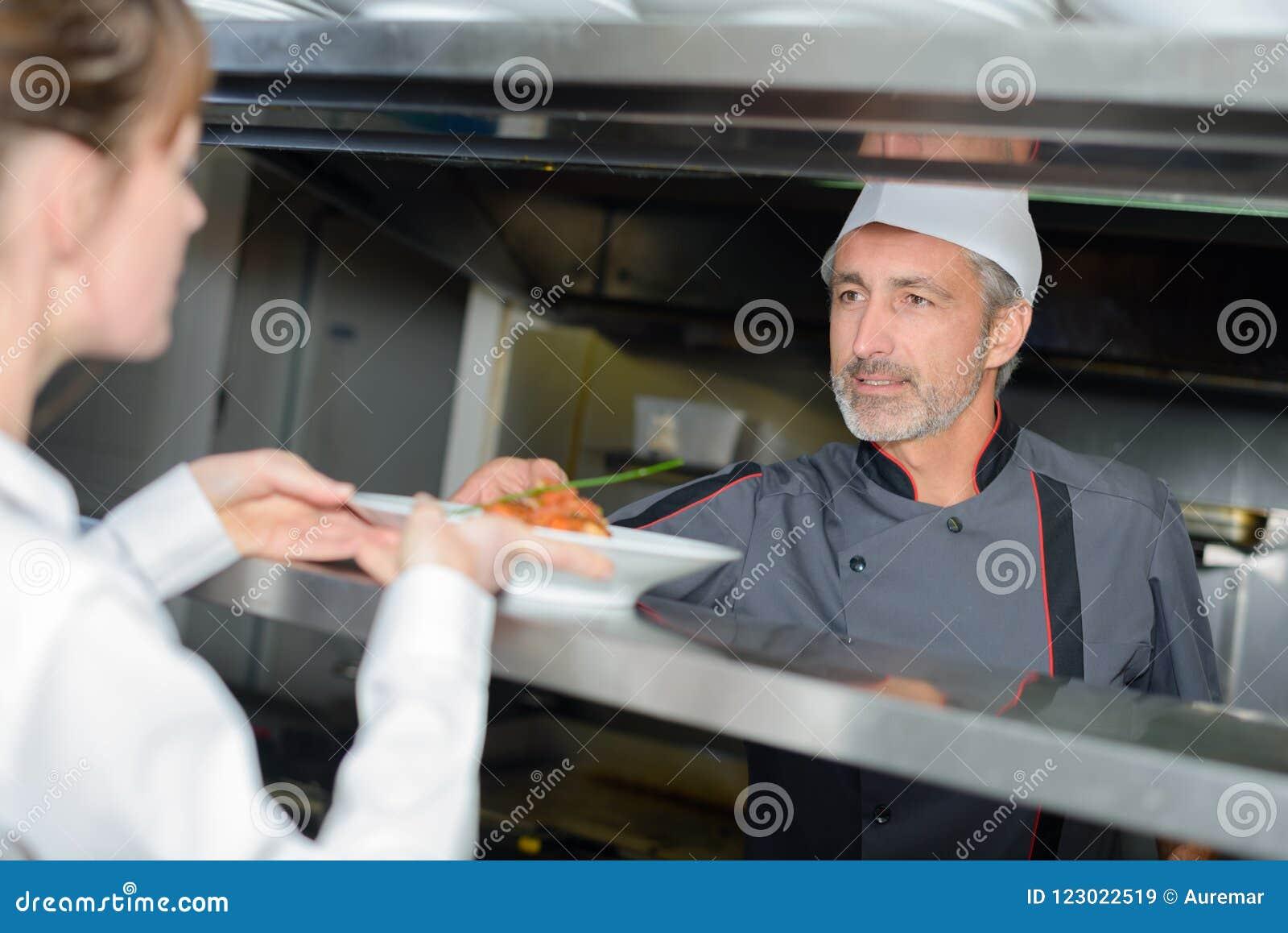 Chef mettant le plat sur la trappe de portion