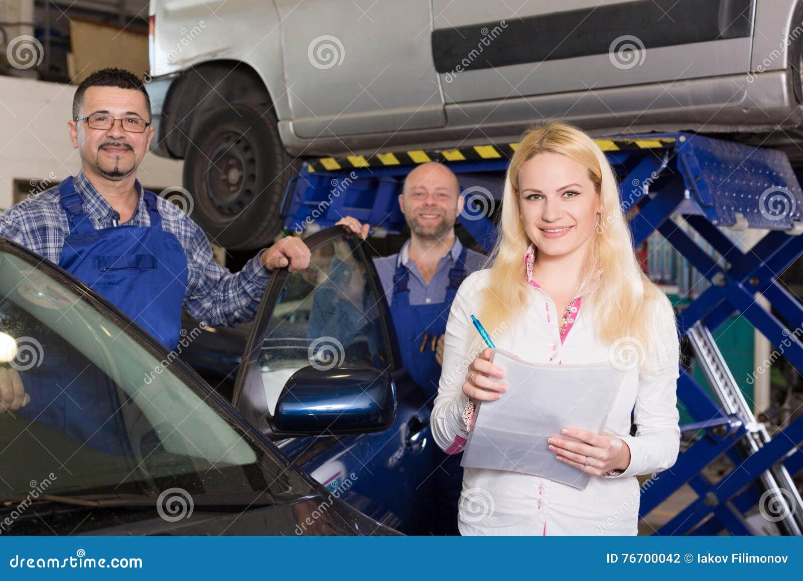 Chef och besättning som gör upp kontrollen av den brutna bilen