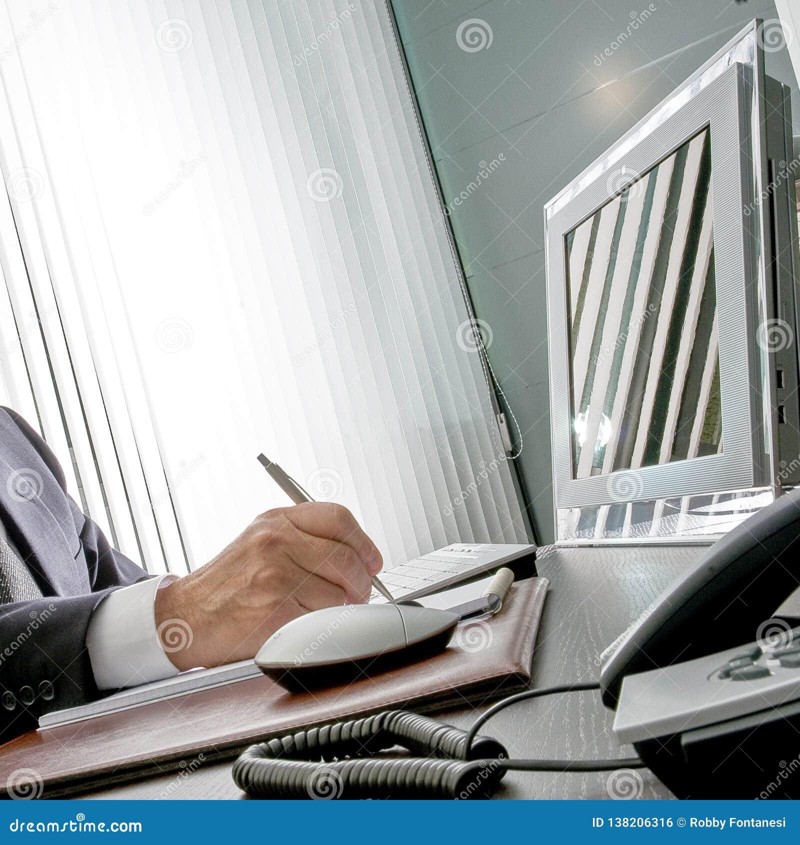 Chef på arbete Den sakkunniga handen av en affärsman som sitter på hans skrivbord, rymmer han pennan framme av hans datorbildskär