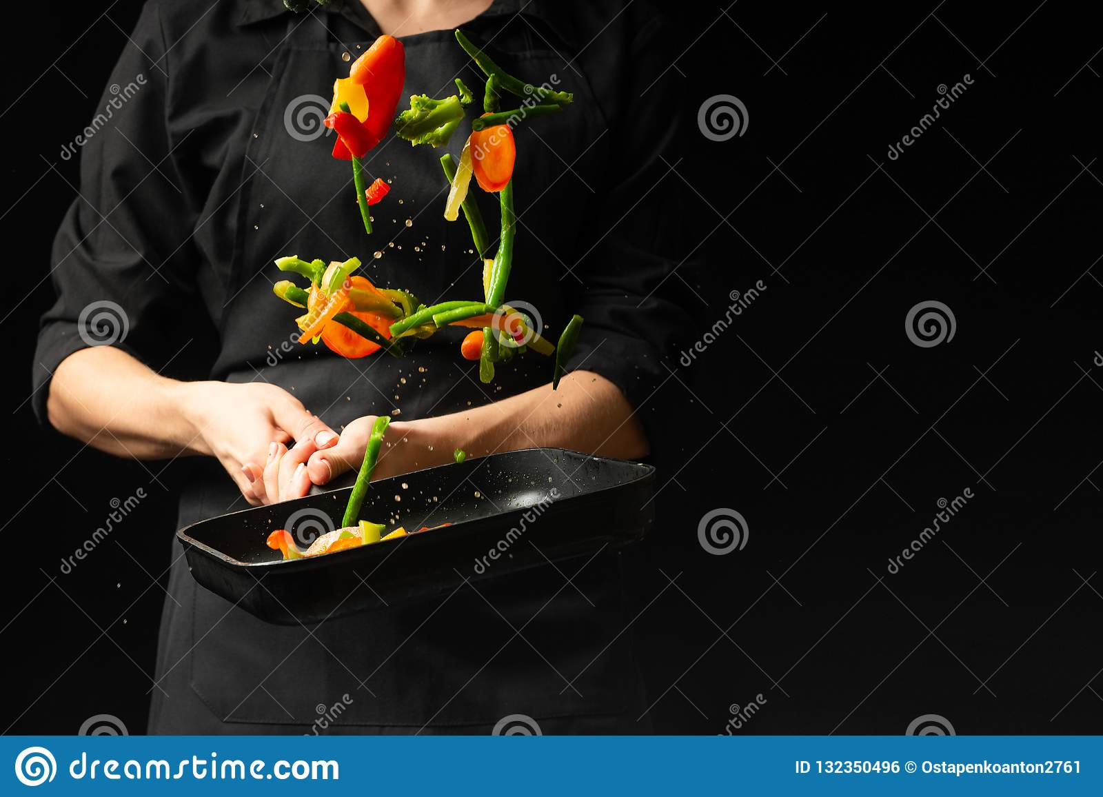 The Chef Prepares The Vegetables On The Pan Black Background For