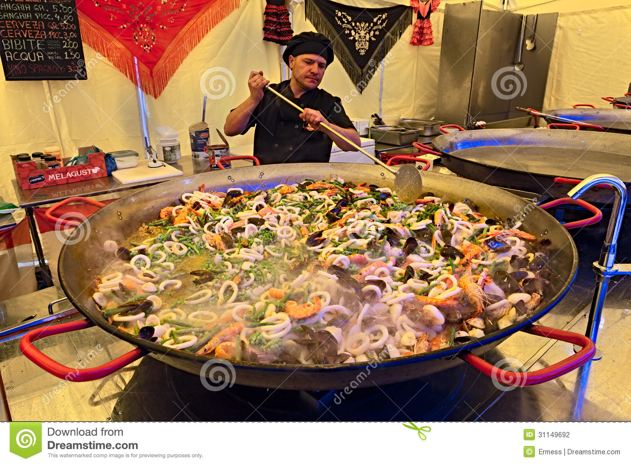 Spanish chef prepares a seafood paella in big pan at the food ...