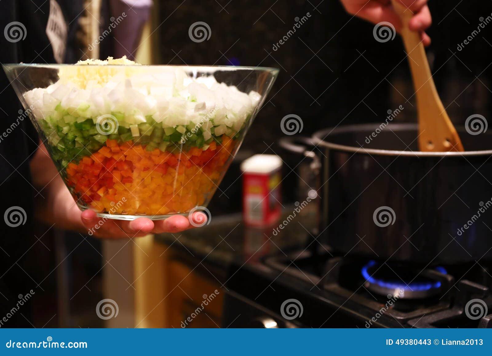chef preparing vegetables at stove in a restaurant kitchen