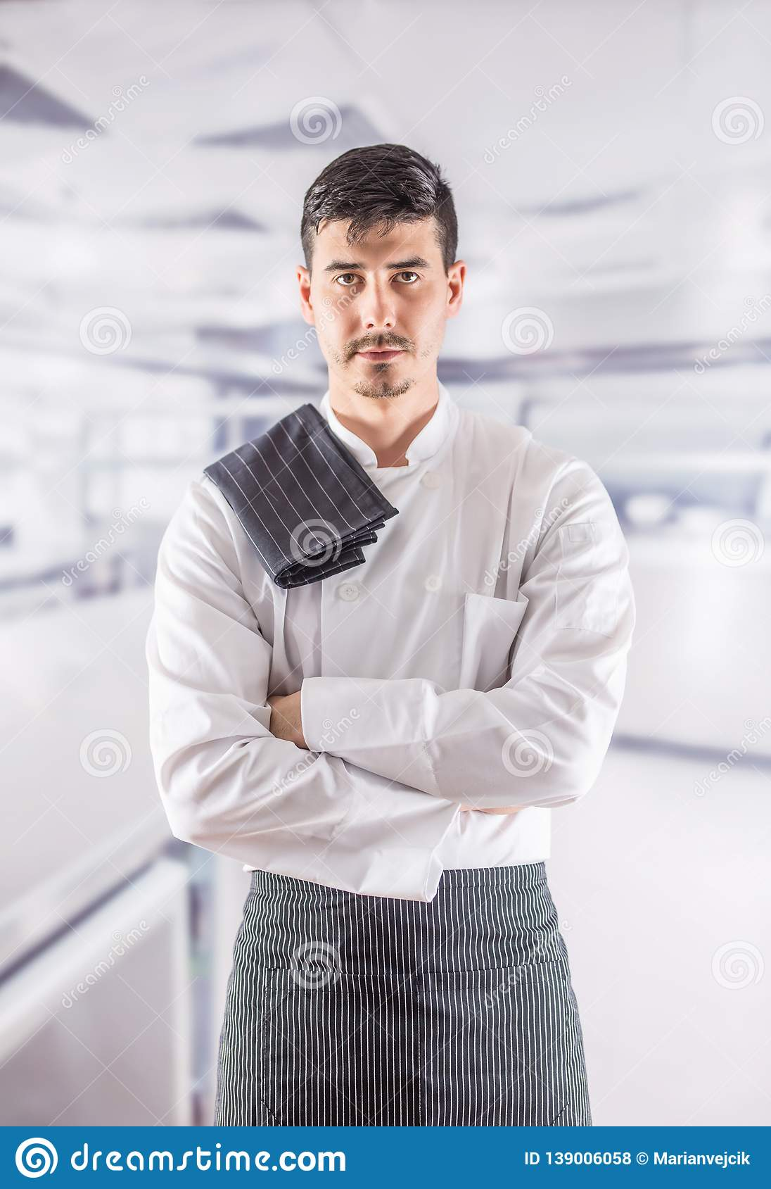 Chef professional in restaurant kitchen standing with towel on shoulder