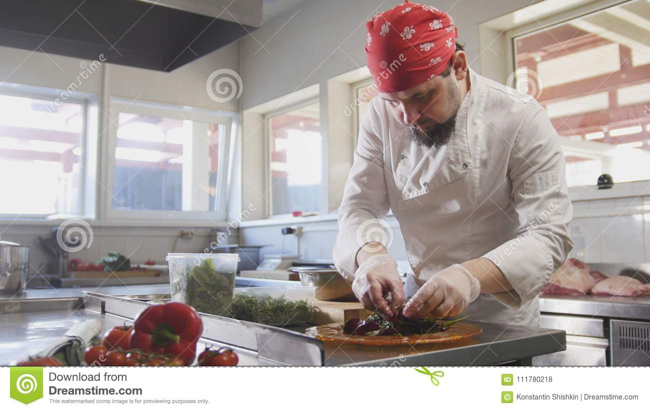 Chef serves the salad by placing the ingredients on a plate
