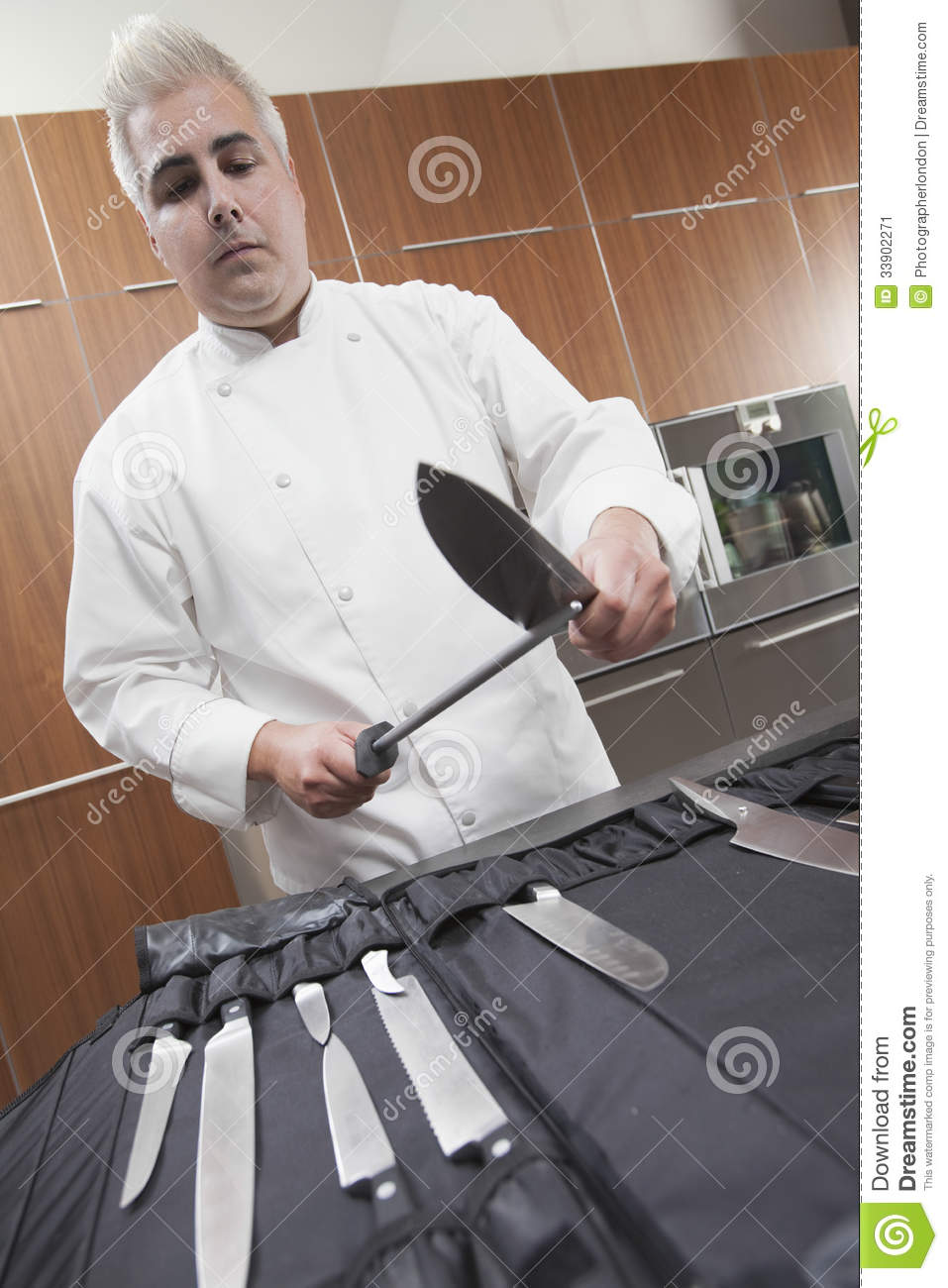 chef sharpening knives in commercial kitchen stock image image 33902271. Black Bedroom Furniture Sets. Home Design Ideas