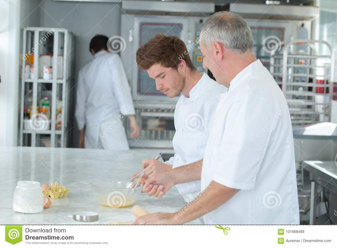 Chef teaching trainee how to become pastry chef