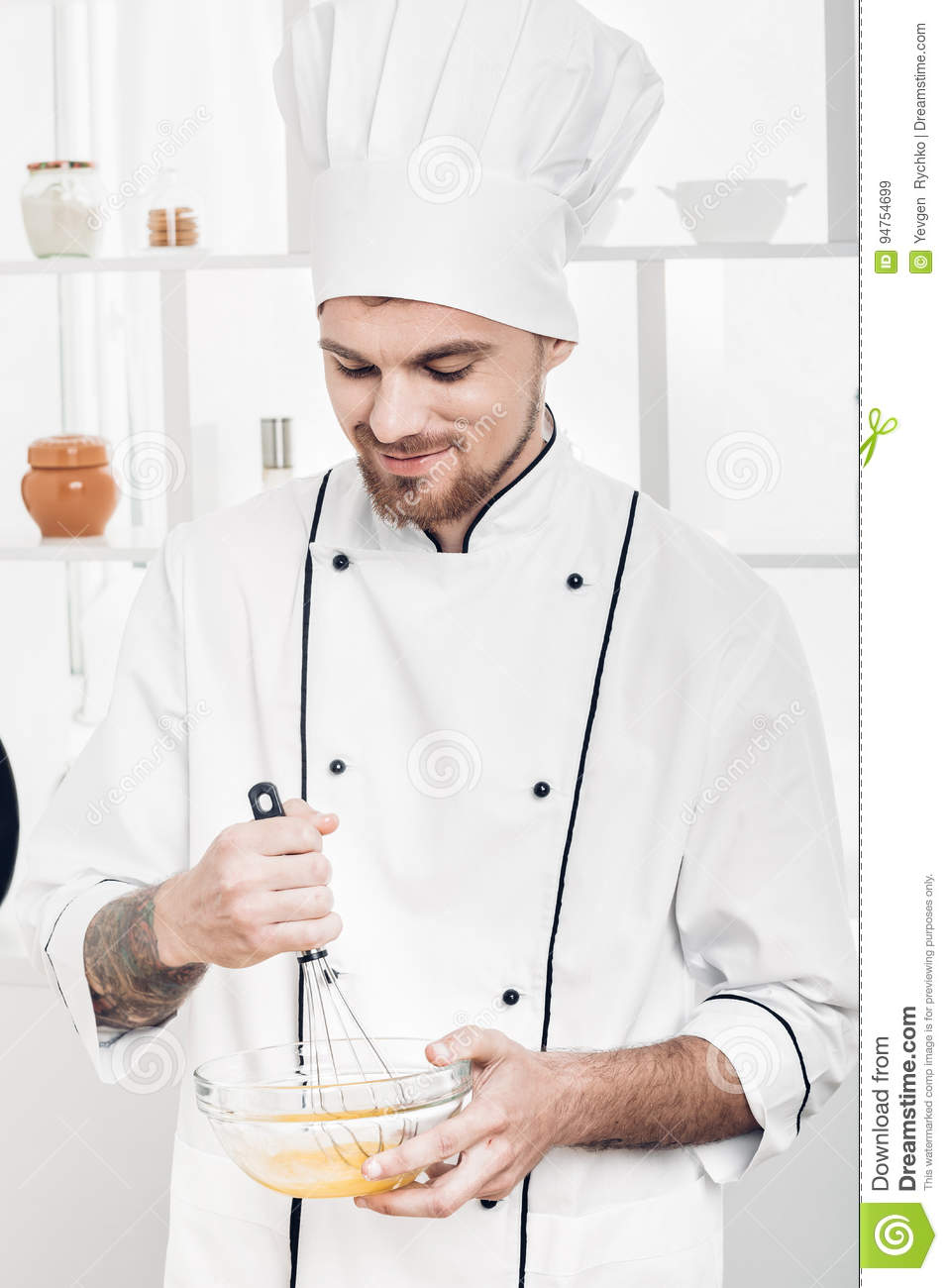 Chef In Uniforms Whipping Eggs And Milk In Bowl In Kitchen