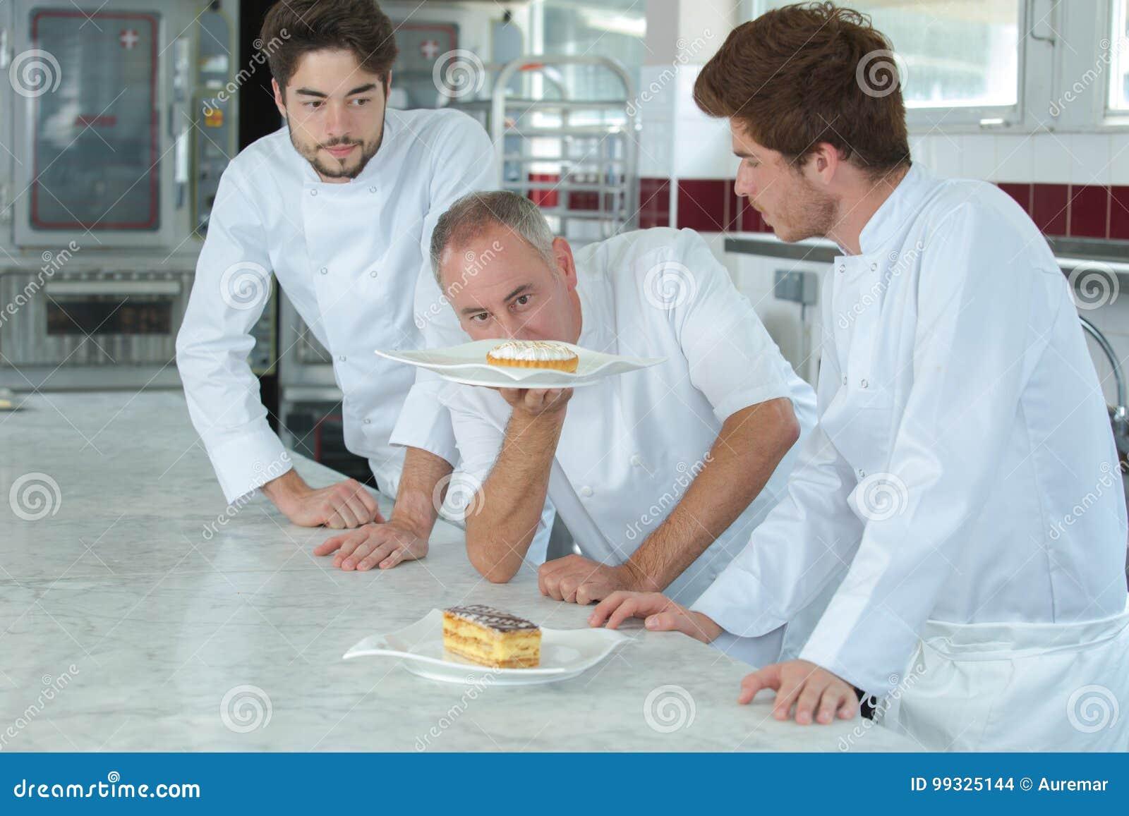 Chef vérifiant des gâteaux d assistants