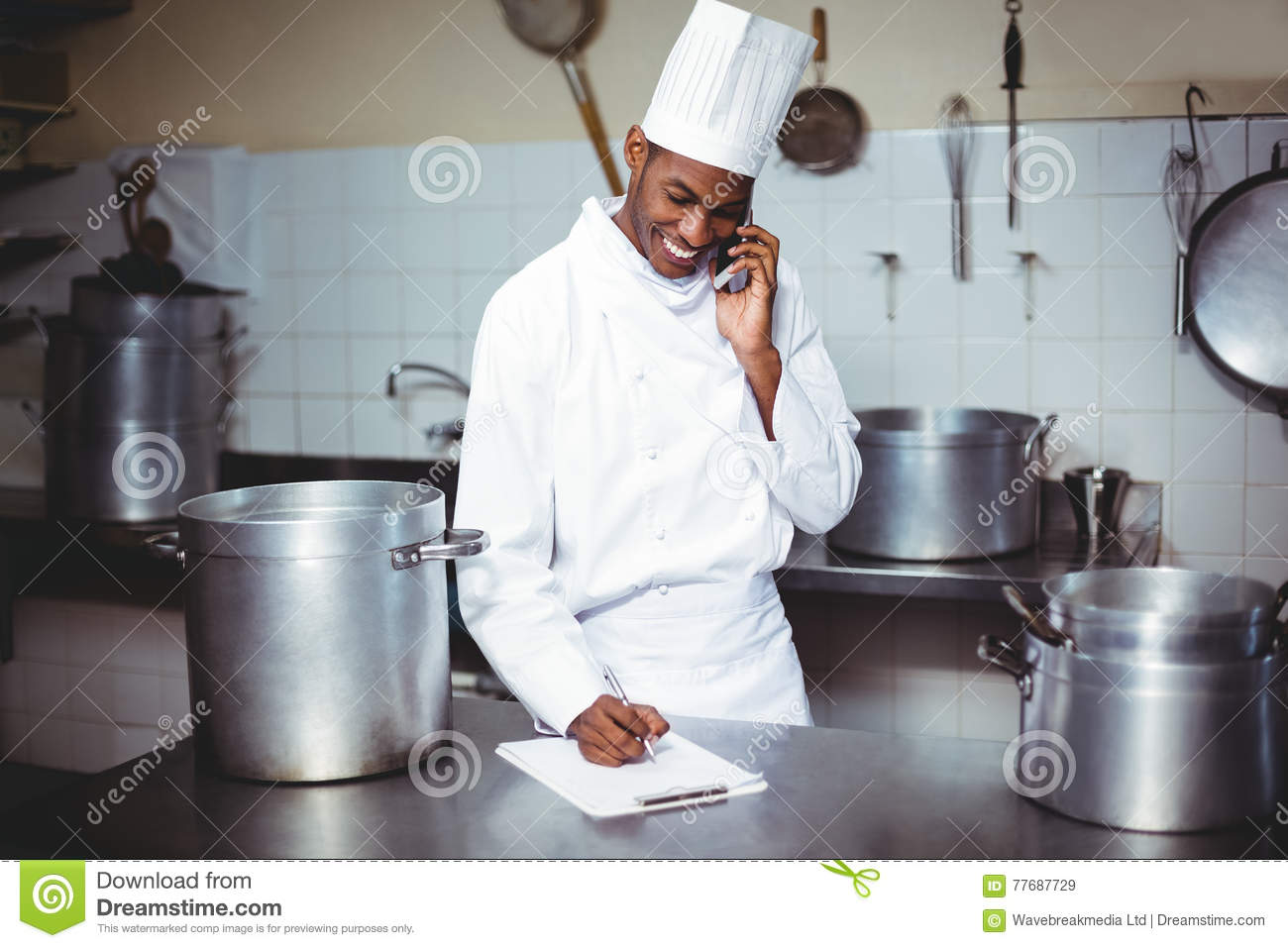 Chef Writing On Clipboard While Talking On Phone Stock Image - Image ...