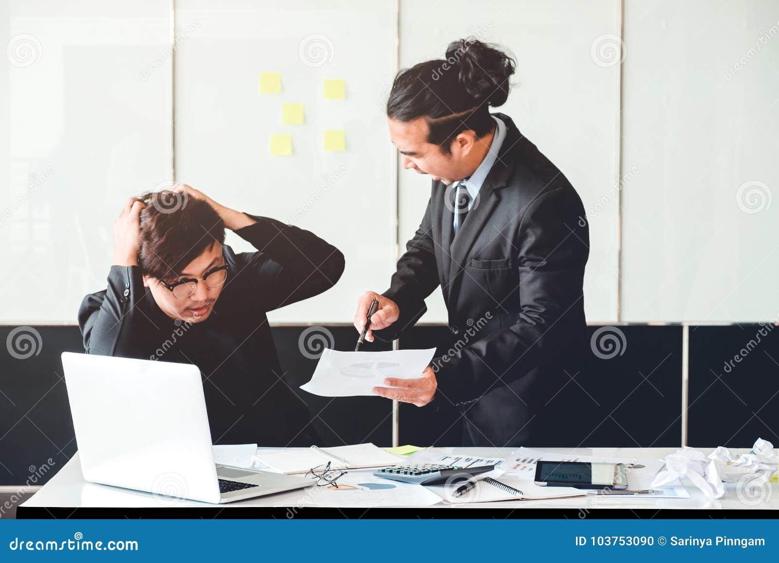 Chefe irritado mau asiático que grita no emplo deprimido triste do homem de negócio