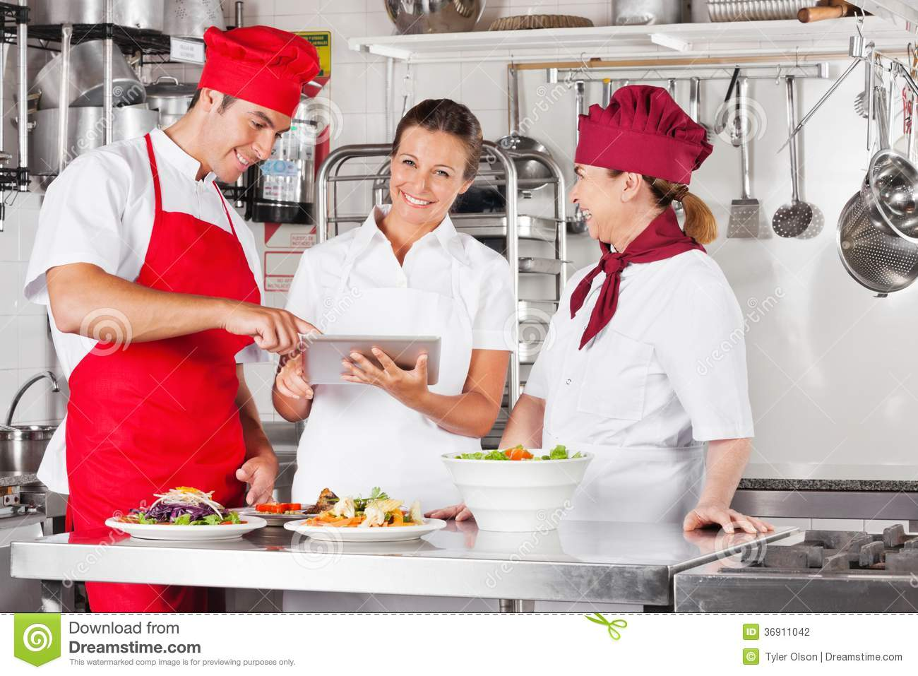 Chefs Using Tablet Computer At Kitchen Counter Stock Photo Image