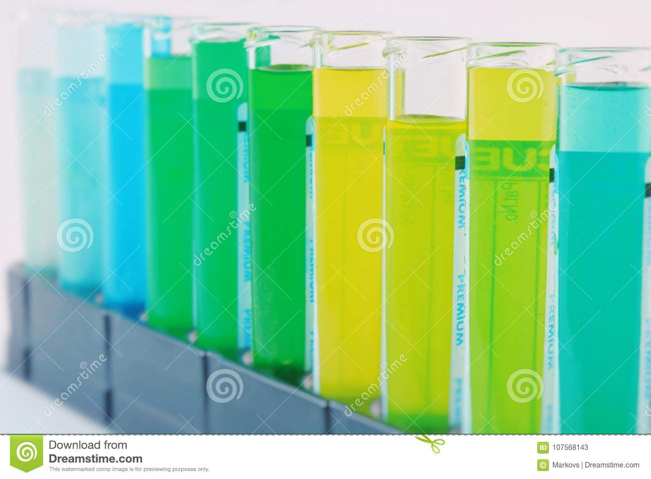 Chemical flasks with multi-colored solutions inside, isolated on white background, set on a black stand
