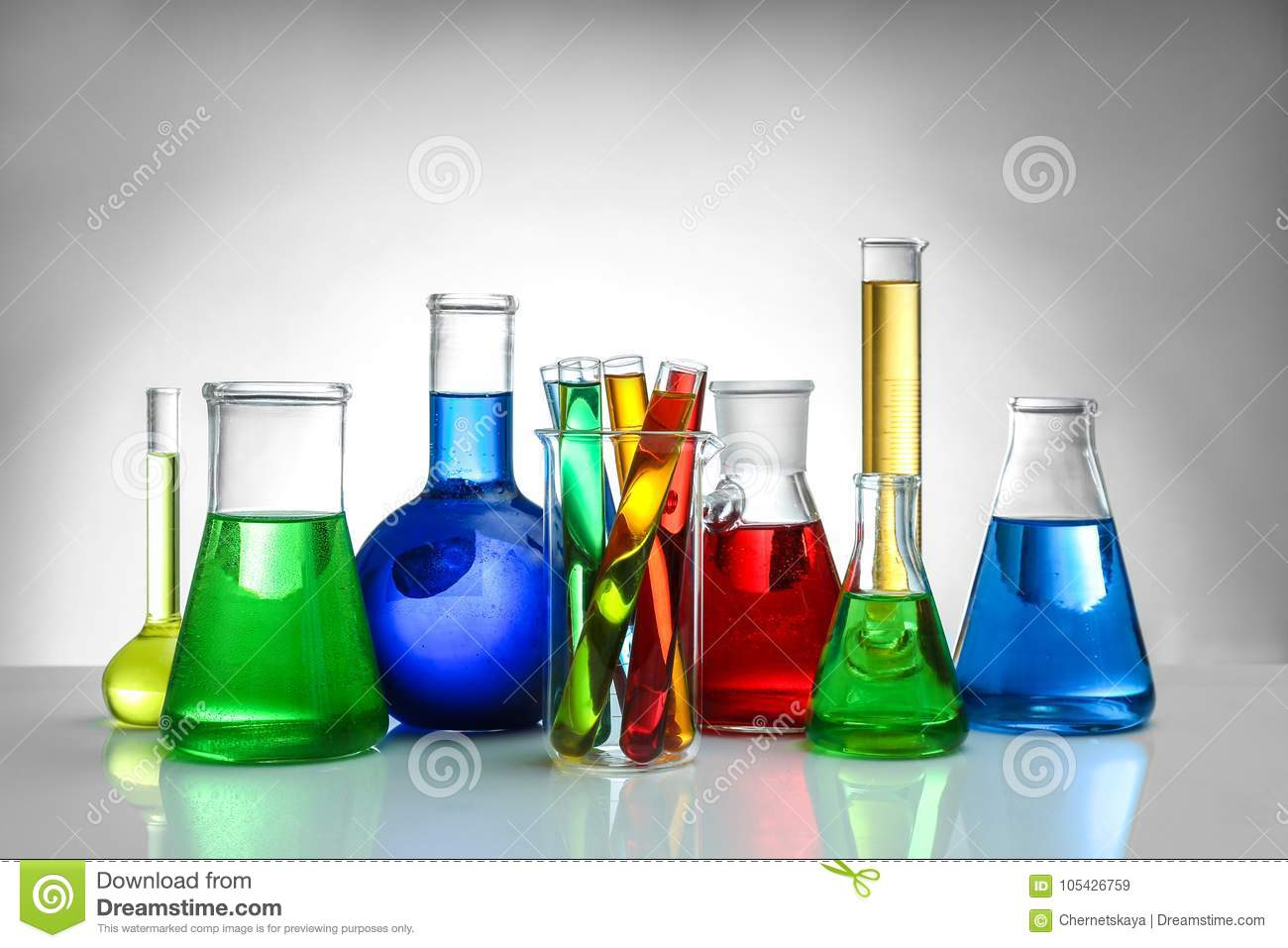 Chemical flasks and test-tubes on background