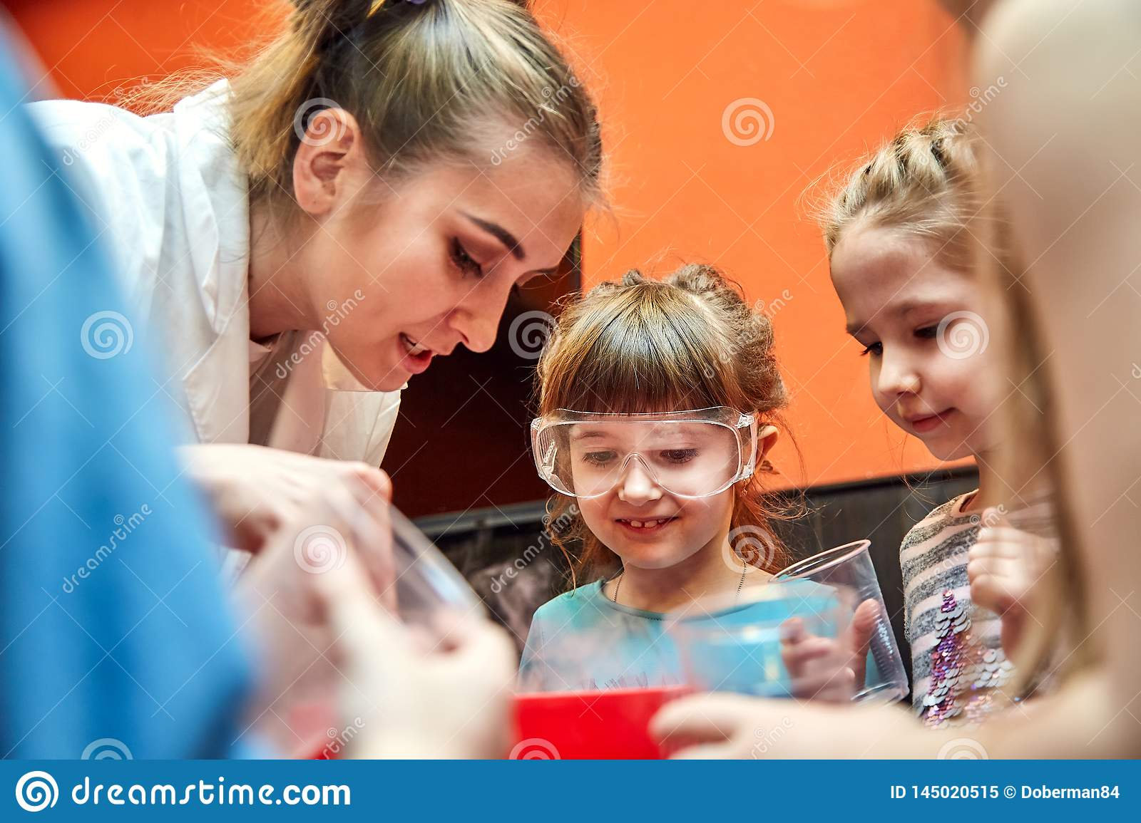 Chemical show for kids. Professor carried out chemical experiments with liquid nitrogen on Birthday little girl.