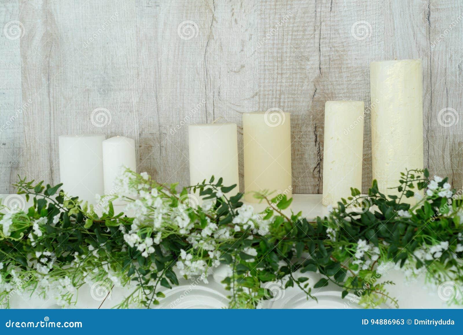 cheminée décorative blanche avec des bougies là-dessus près du mur