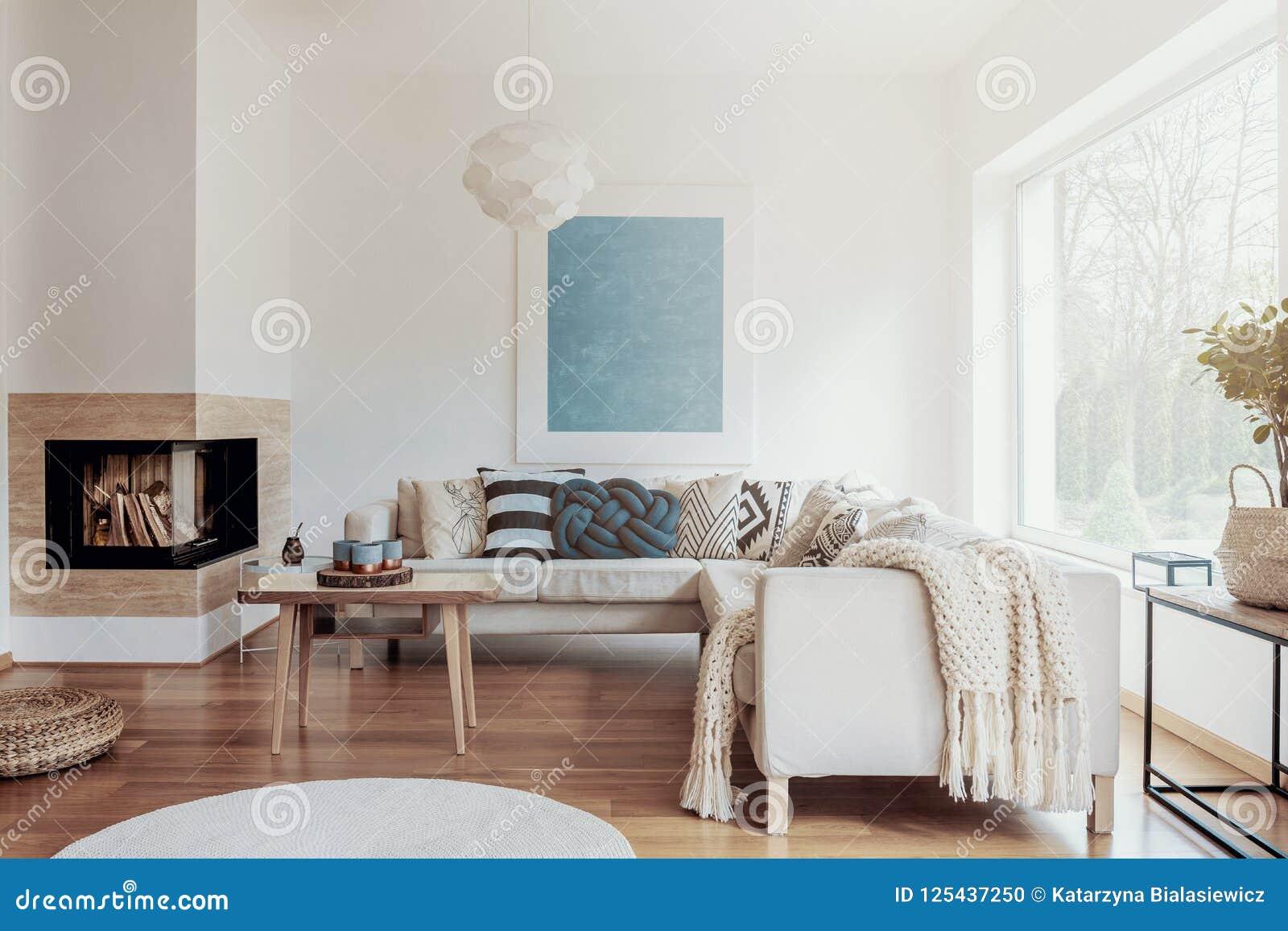 Cheminée faisante le coin moderne dans un intérieur ensoleillé et paisible de salon avec les murs blancs et des oreillers et des