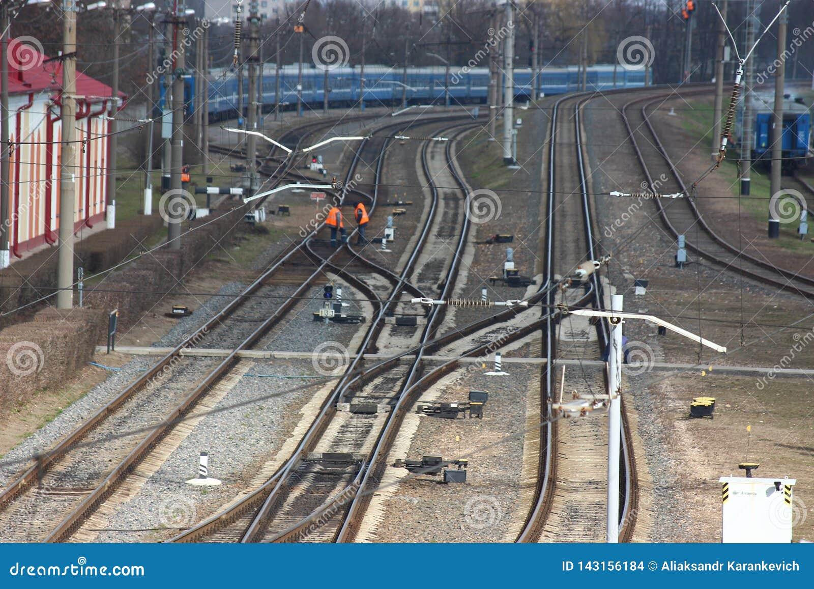 Chemin de fer de station de distribution rails et dormeurs, le personnel de la gare ferroviaire dans l habillement spécial répara