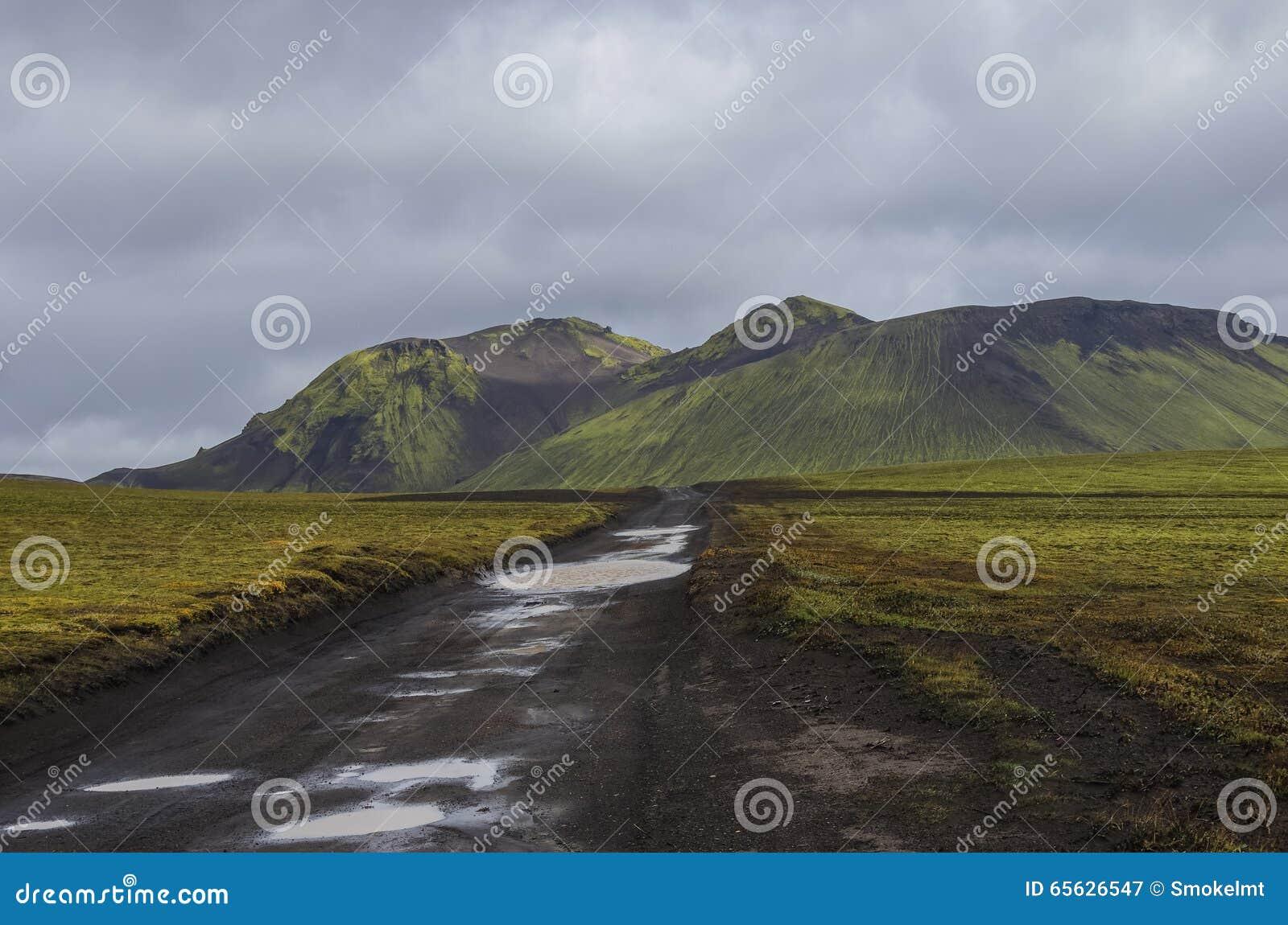 Chemin de terre après pluie et montagnes volcaniques couvertes de mousse Landma