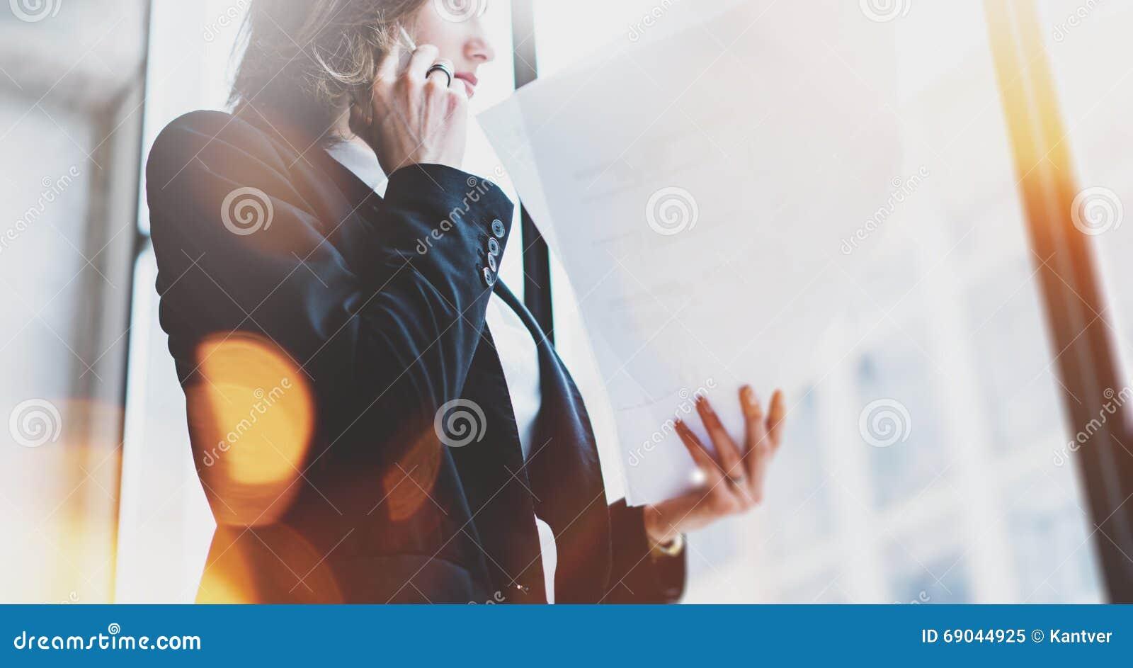 Chemise blanche de port de femme d affaires de photo, smartphone parlant et documents de se tenir dans des mains Bureau de grenie