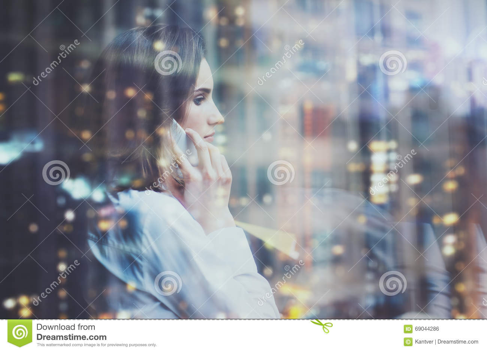 Chemise blanche de port de femme de photo, smartphone parlant et tenir des plans d action dans des mains Bureau de grenier de l e