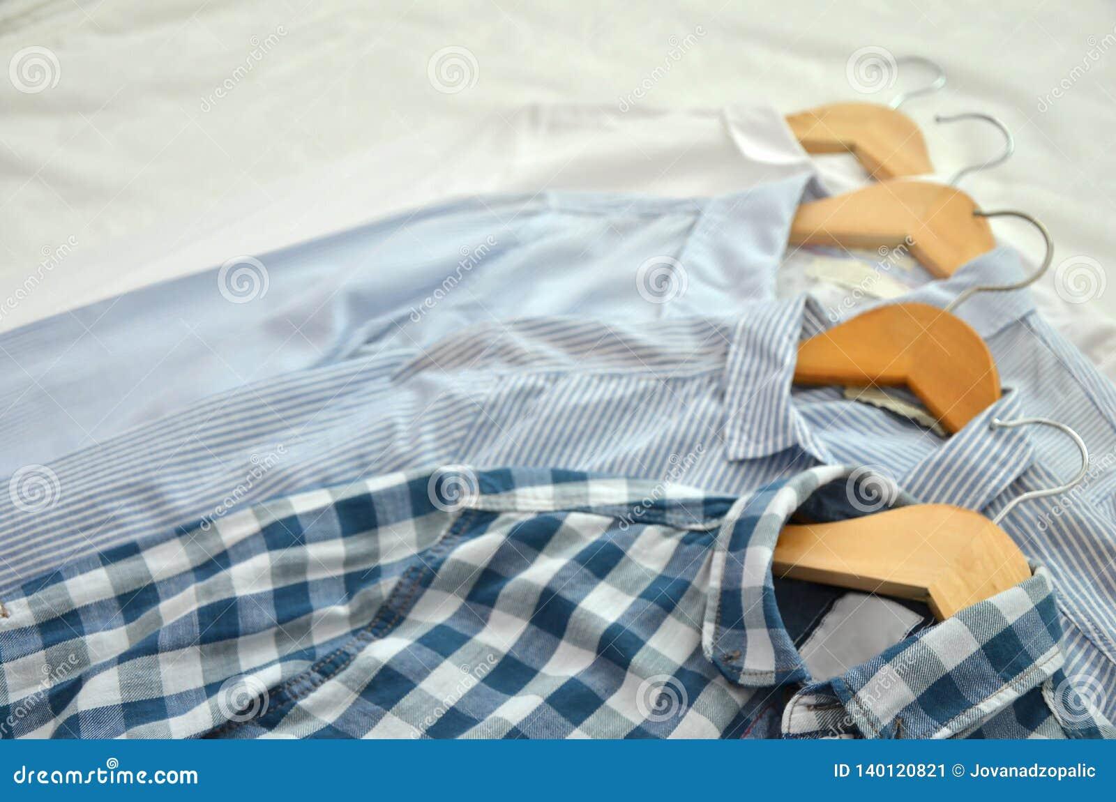4 chemises sur les chaises en bois placées sur le lit dans les nuances du blanc,