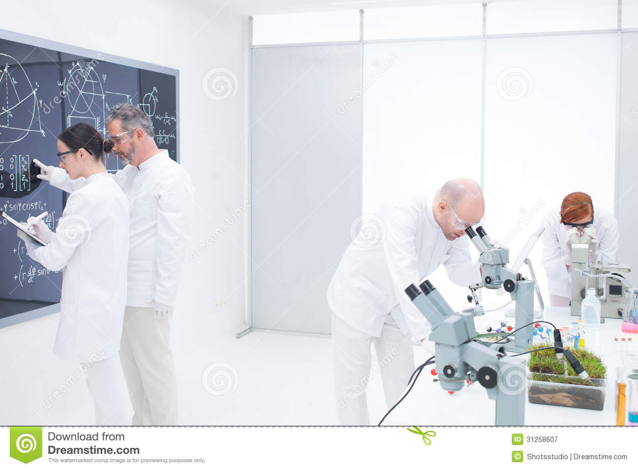 General view of a teacher in a chemistry lab pointing formulas on a