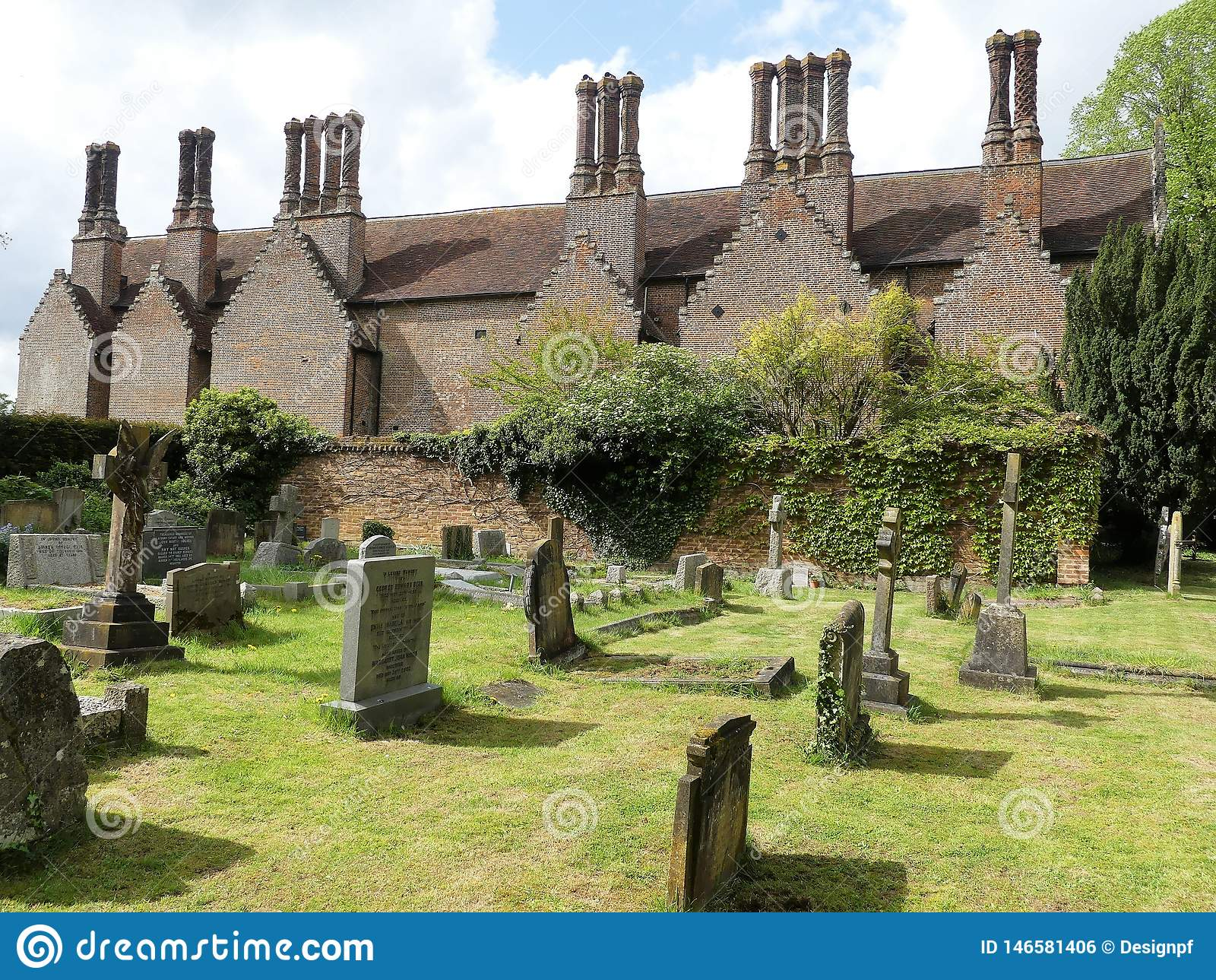 Chenies Manor House, a Tudor Grade I listed building, with church graveyard in foreground