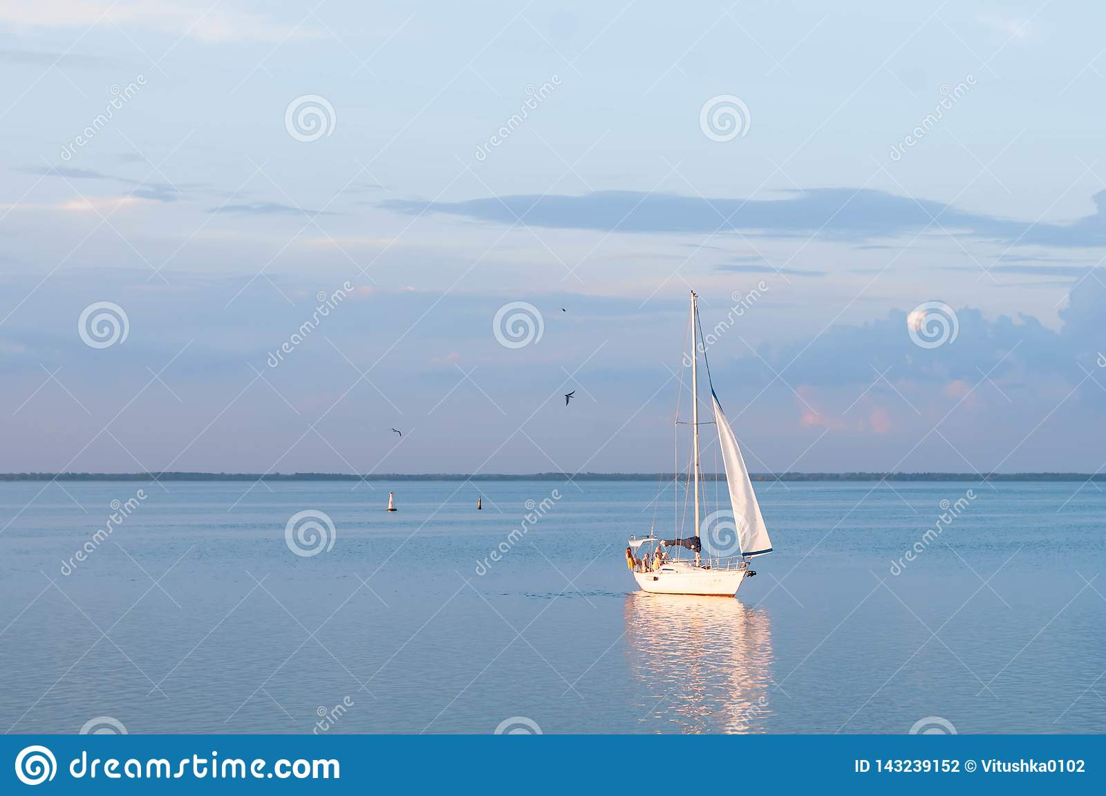Cherkasy, Ukraine - 07.20.2018: white sailing boat sails on river and casts orange glowing reflection