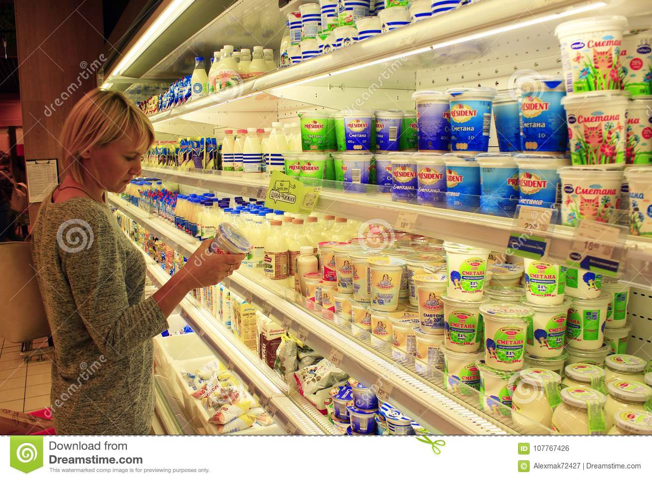 Woman makes her choice in the shop of dairy products