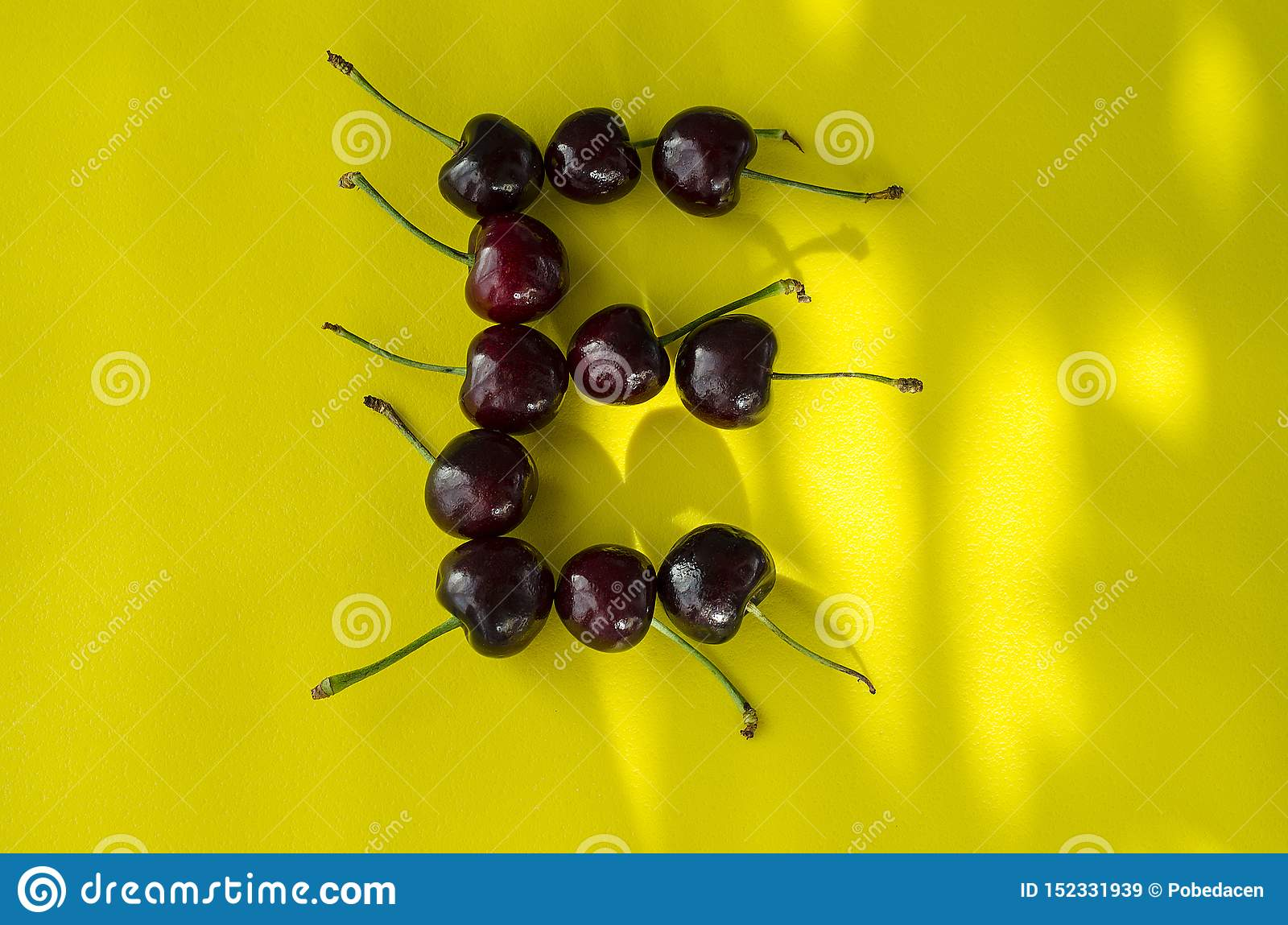 Cherry berries on a bright yellow background in the form of the letter E with sun highlights