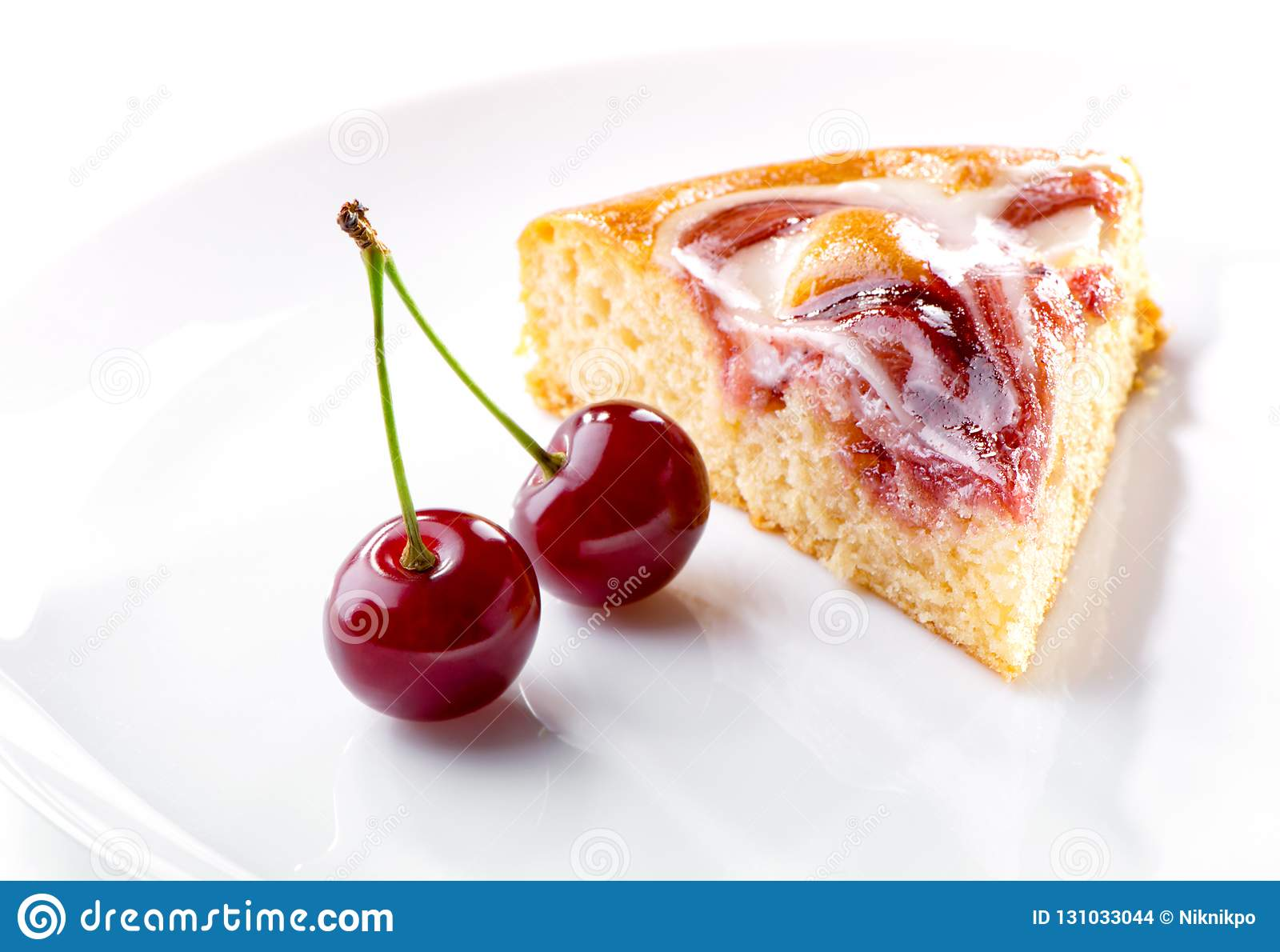 Cherry berries and piece of cream fruit pie on white plate close-up