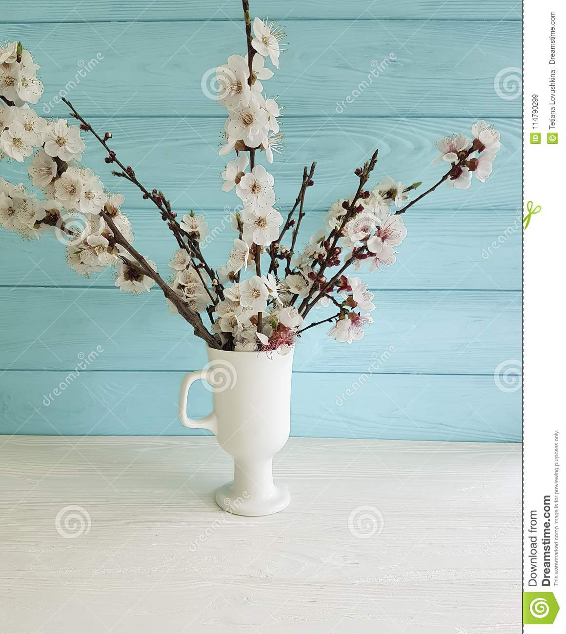 Cherry blossom branch floral decorative beautiful in a vase on a colored wooden background, spring,bouquet