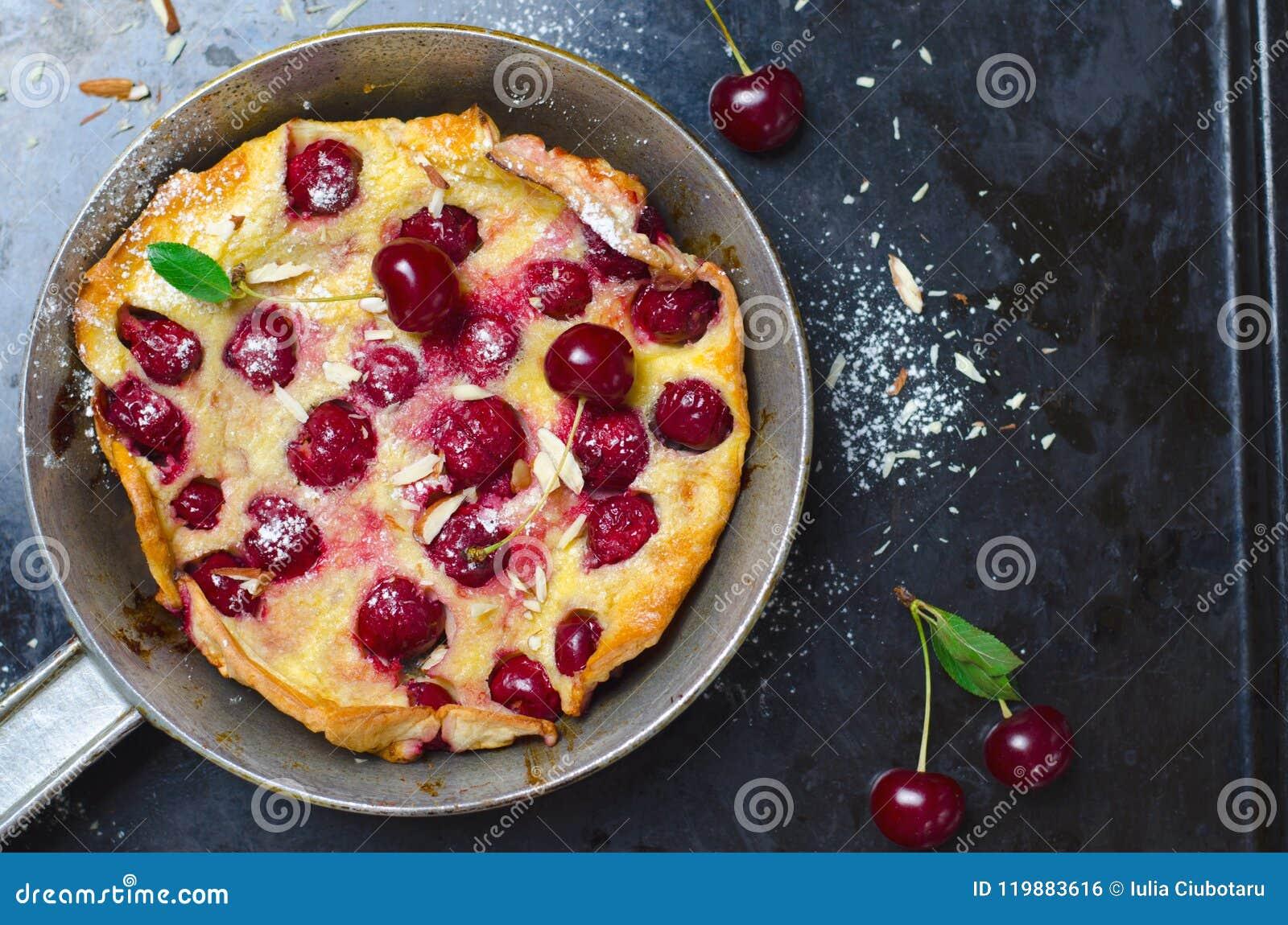 Cherry Dutch Baby tysk pannkaka för Puff på tappningpannor och mörk bakgrund, hemlagad sommarefterrätt