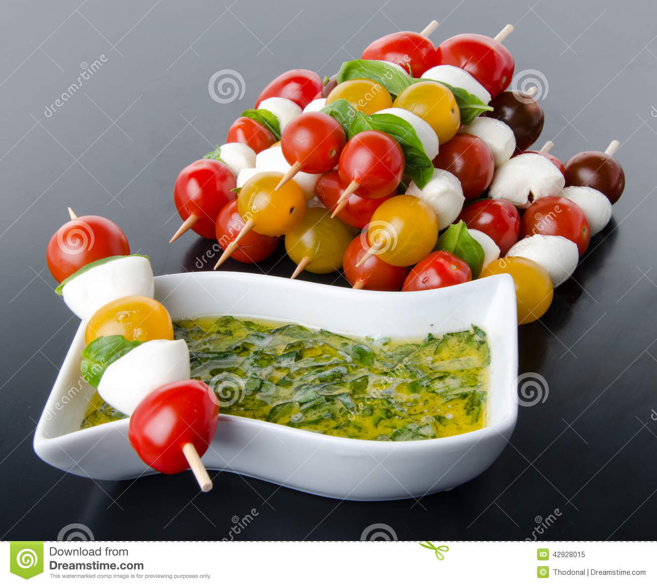 Cherry tomatoes and mozzarella on skewers and a vinaigrette sauce with basil