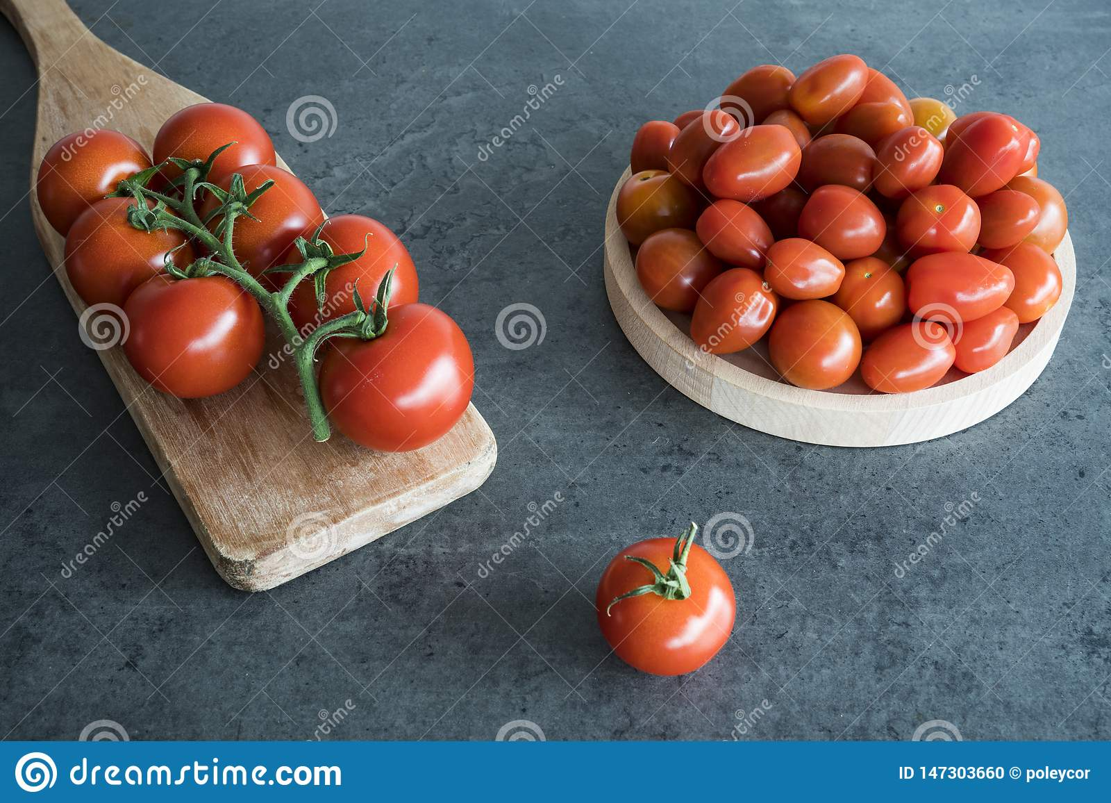 Cherry tomatoes on wooden plate and cutting board,