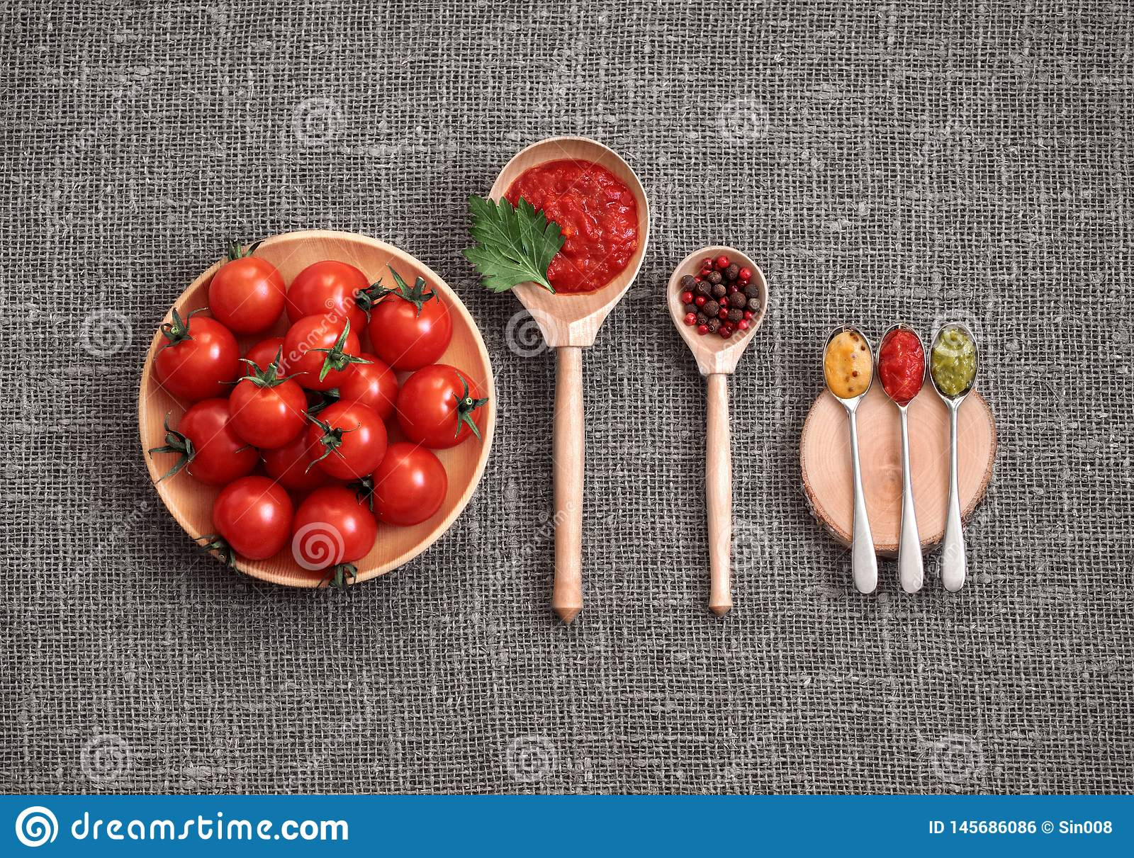 Cherry tomatoes in a wooden plate on a gray background. Adjika sauce, red and black pepper, parsley, mustard and pesto in spoons