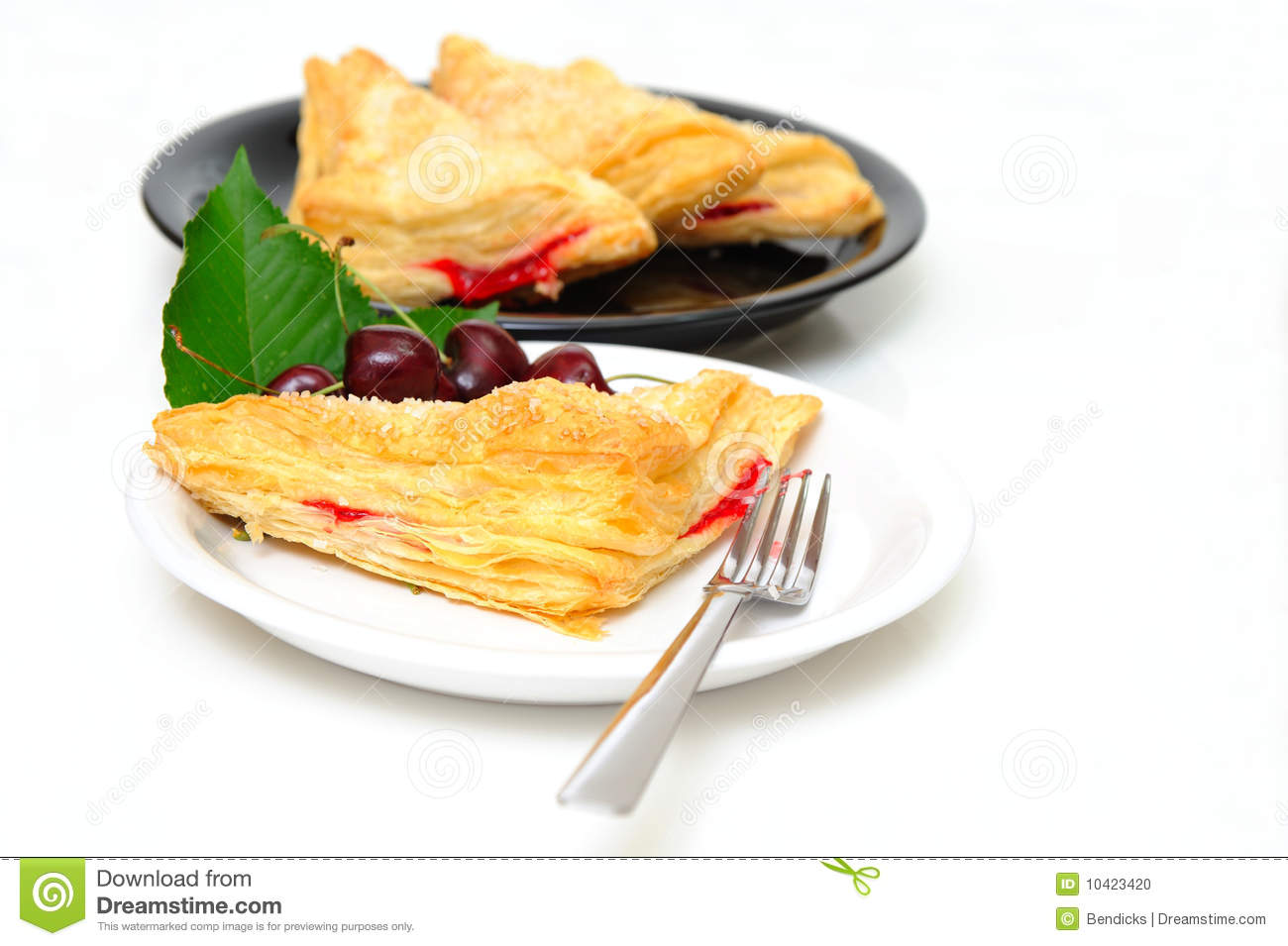 Cherry turnovers with fresh cherries on a white saucer with adiitional ...