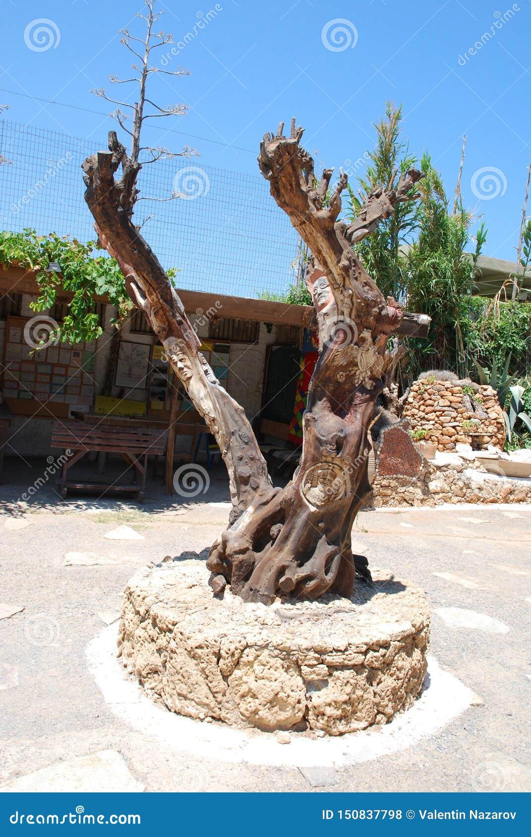 Chersonissos, Chipre, Grécia - 31 07 2013: escultura da madeira no meio do jardim das plantas e das flores na Creta