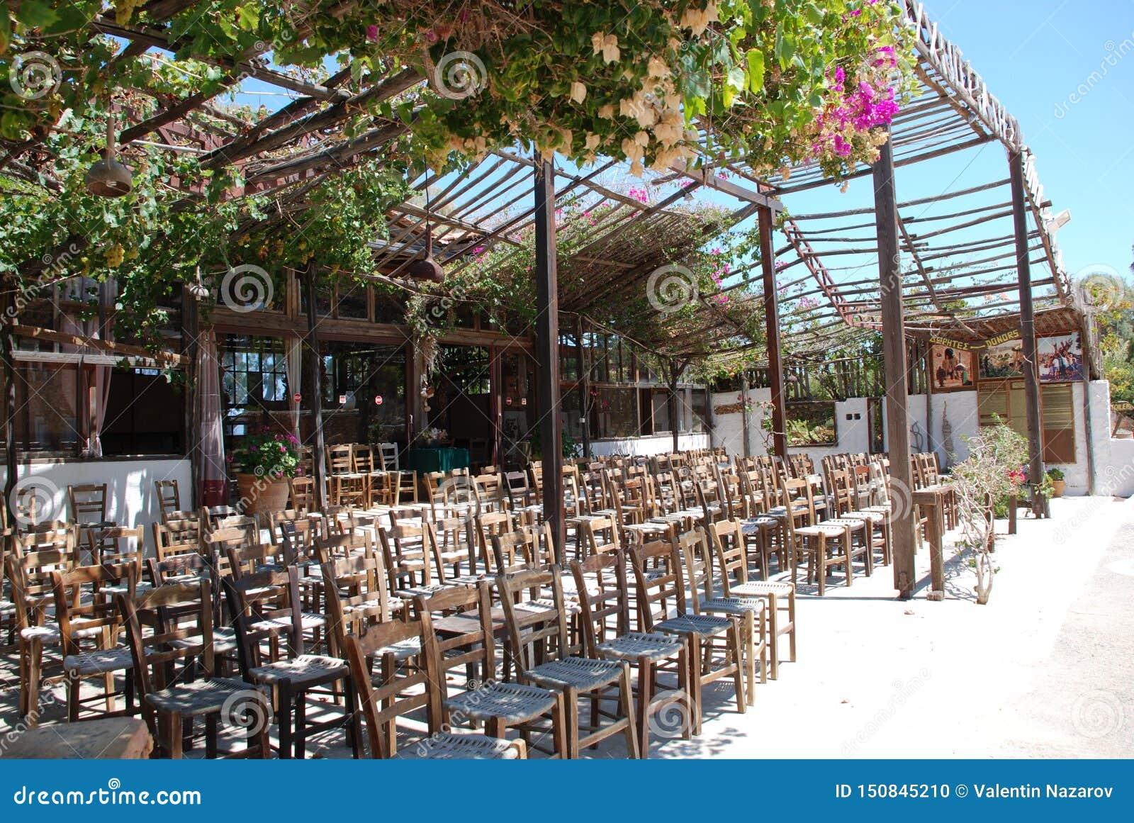 Chersonissos, Chipre, Grécia - 31 07 2013: muitas cadeiras no jardim sob o céu quente do verão e um dossel das flores