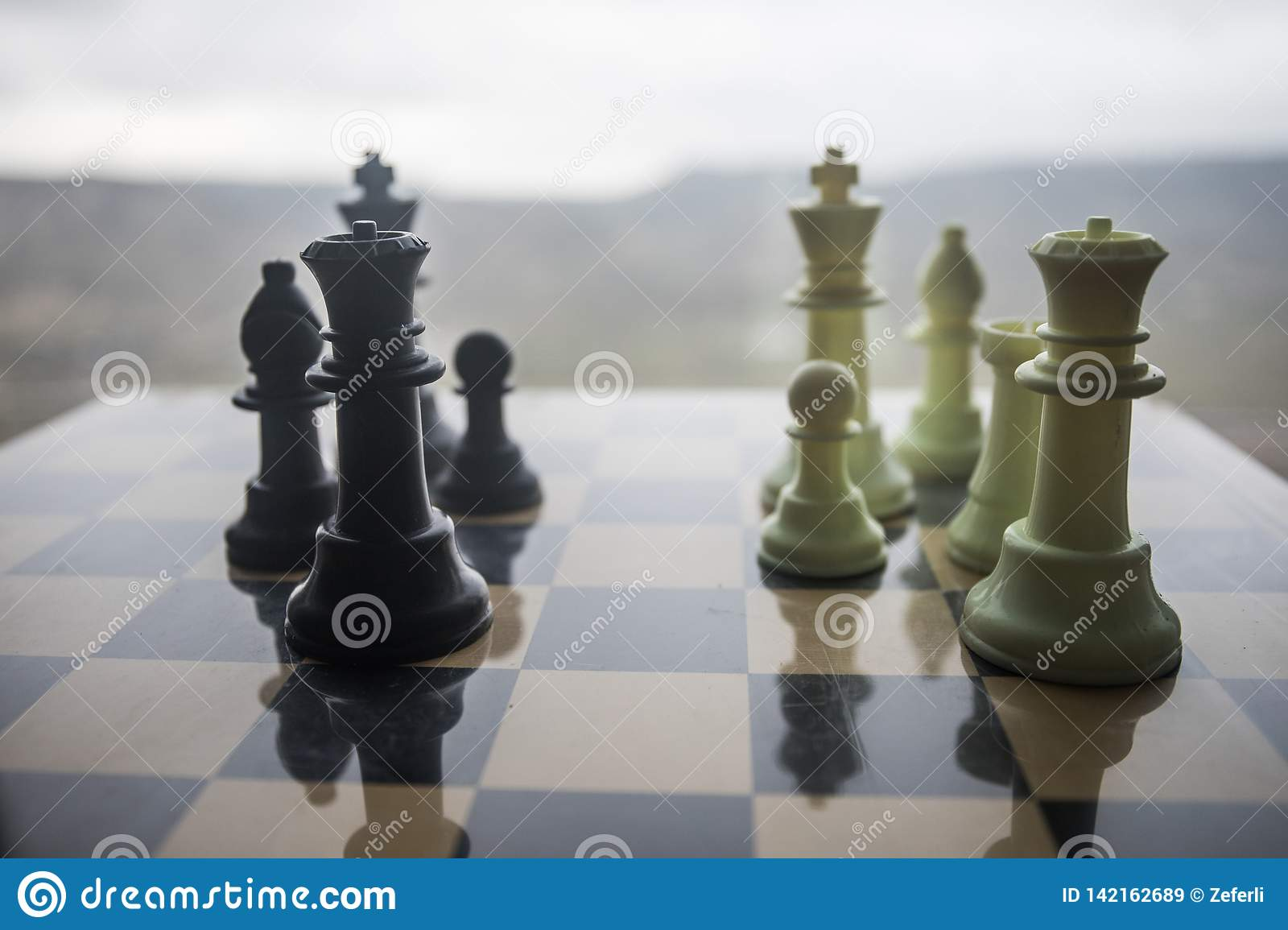 chess board game concept of business ideas and competition and strategy ideas. Chess figures on a chessboard outdoor sunset