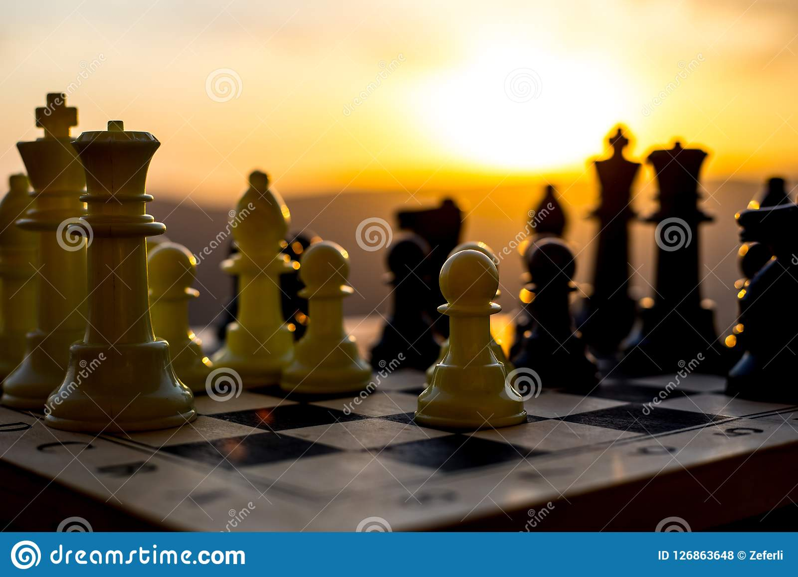 chess board game concept of business ideas and competition and strategy ideas. Chess figures on a chessboard outdoor sunset backgr